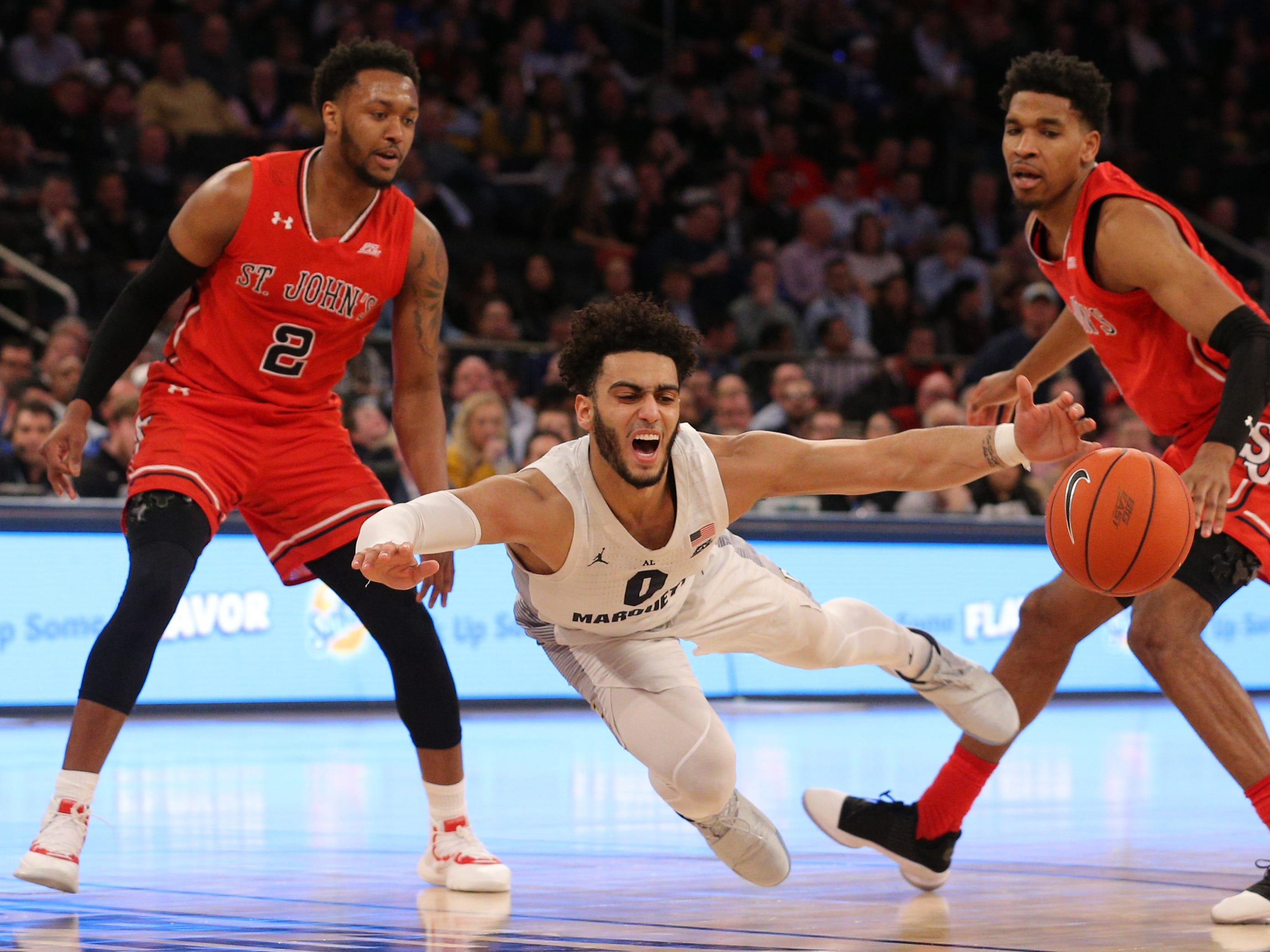 Marquette's Markus Howard falls to the floor after he is fouled by St. John's  guard Justin Simon (right) in front of St. John's guard Shamorie Ponds.