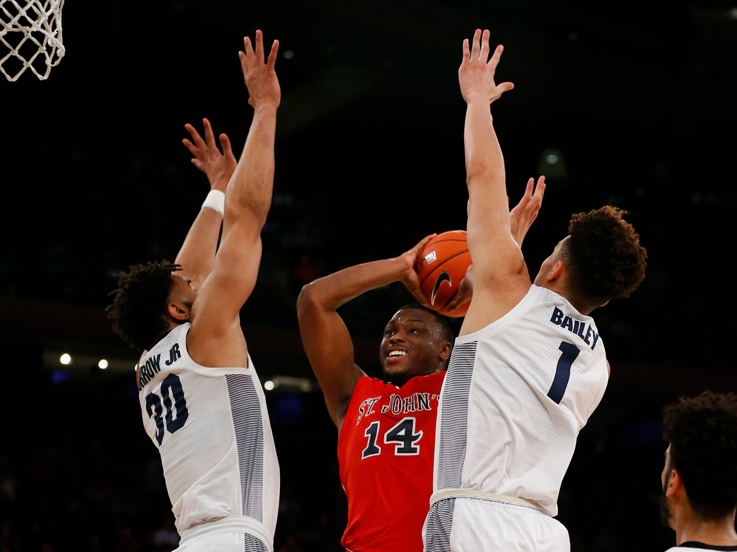 Marquette Golden Eagles forwards Ed Morrow and Brendan Bailey close in on St. John's guard Mustapha Herron.