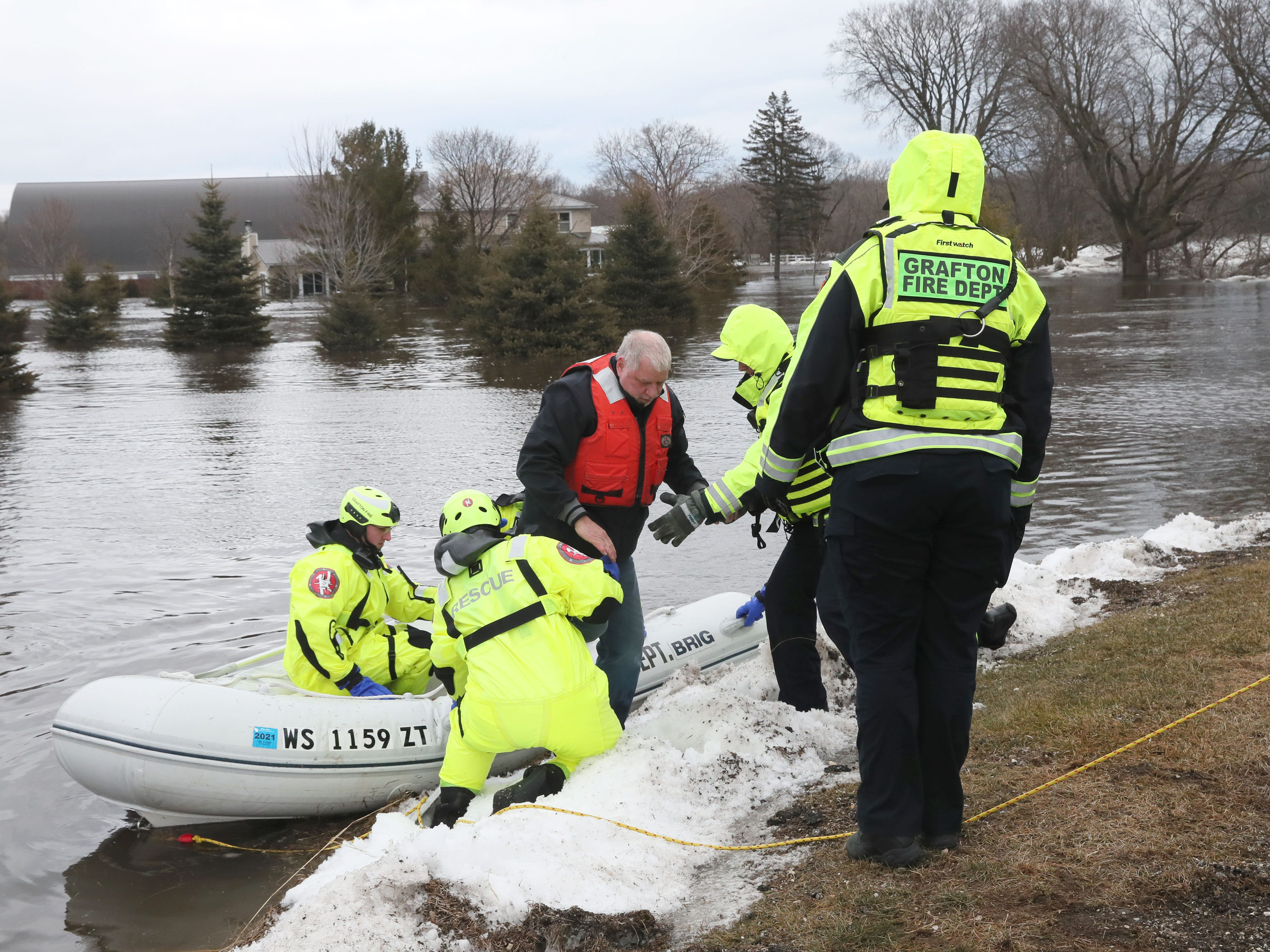Grafton firefighters help a man out of their boat that they brought to dry land from his home at the Riverview Kennel property. March 15, 2019 Grafton firefighters rescued two people from the Riverview Kennel on the Milwaukee River at  1584 Pioneer Rd in Cedarburg.  Ice going out on the river was blocked by bridge diverting flow over the Cty Highway C and the surround low areas.