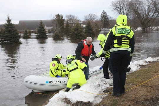 Grafton firefighters help a man out of their boat that they brought to dry land Friday from his home at the Riverview Kennel property. Grafton firefighters rescued two people from the property on the Milwaukee River at 1584 Pioneer Rd. in Cedarburg.