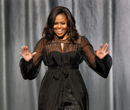 "Former first lady Michelle Obama greets the audience as she arrives on stage for ""Becoming: A Conversation with Michelle Obama""  at the Miller High Life Theatre."