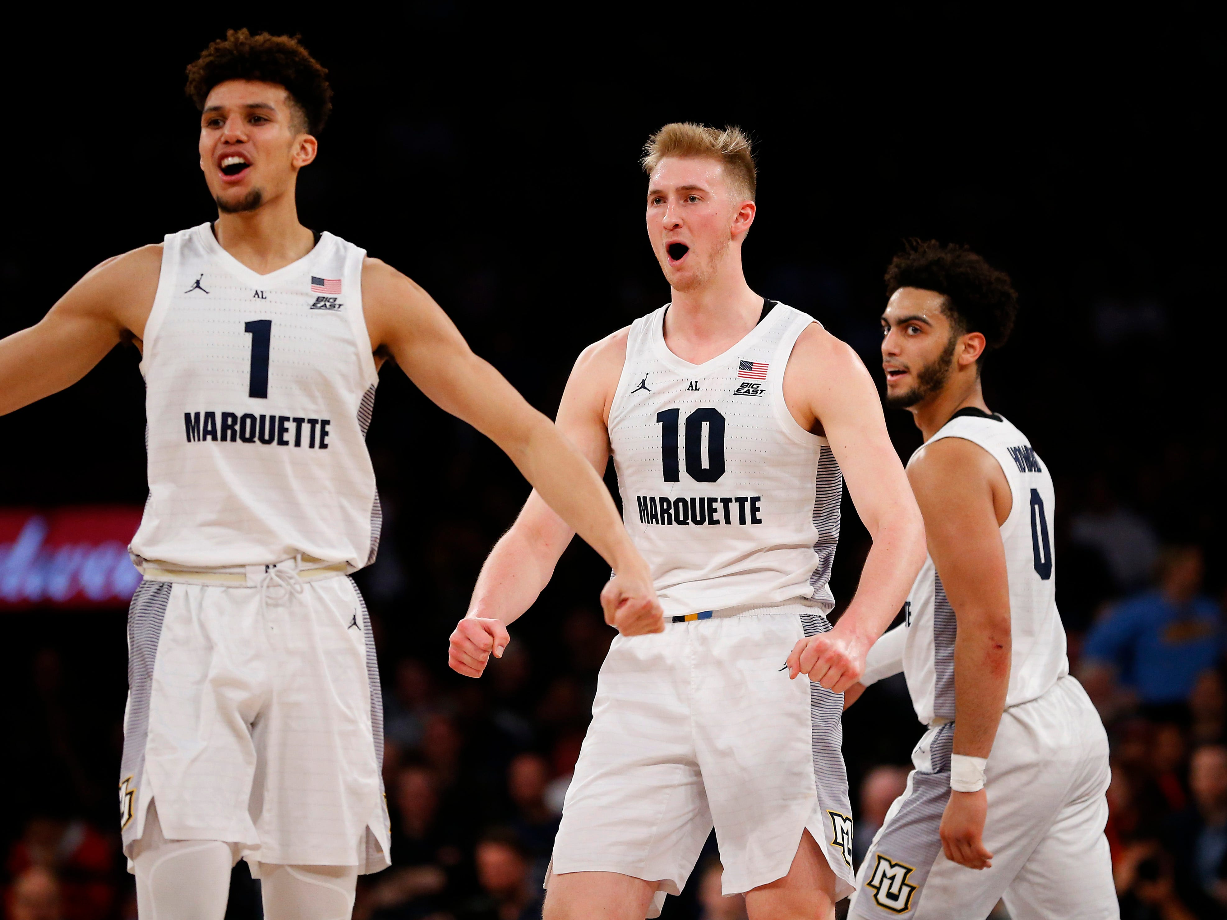 Brendan Bailey,  Sam Hauser and Markus Howard celebrate a basket  during Marquette's scoring spurt in the second half that puts the game out of reach.