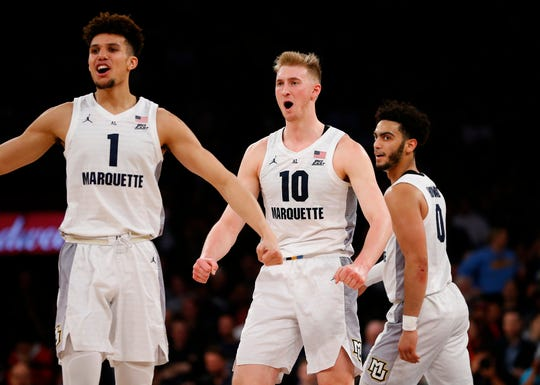 Marquette forwards Brendan Bailey and Sam Hauser (middle)and guard Markus Howard celebrate during Marquette's game-clinching run Thursday night.