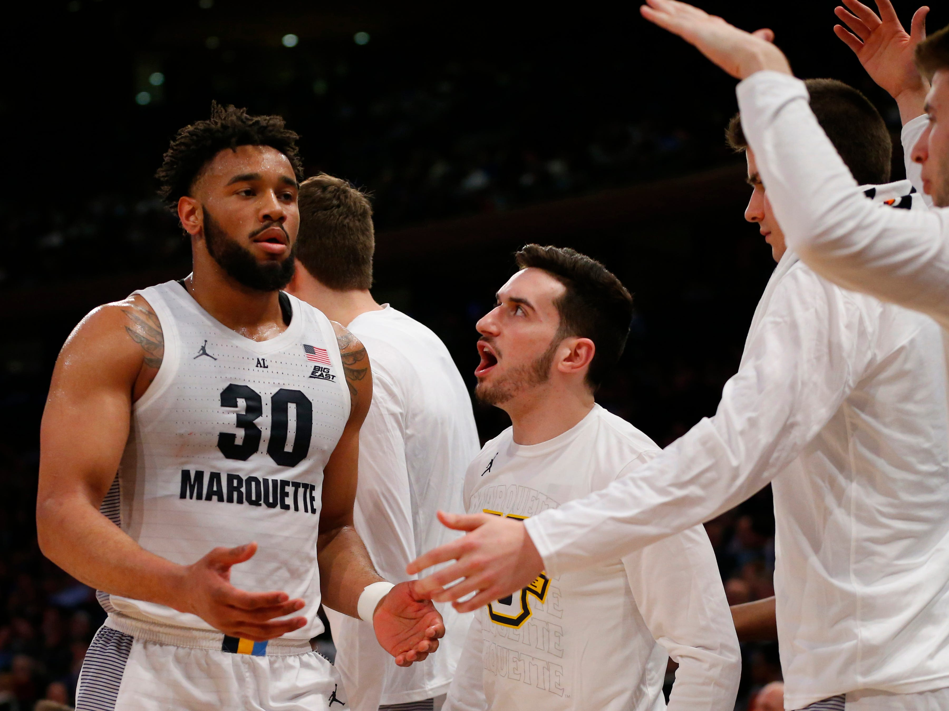 Marquette teammates meet Ed Morrow at the bench in the second half.