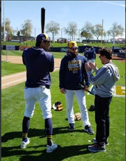 Christian Yelich,  Baker Mayfield  and Mark Attanasio talk at Brewers spring training camp.