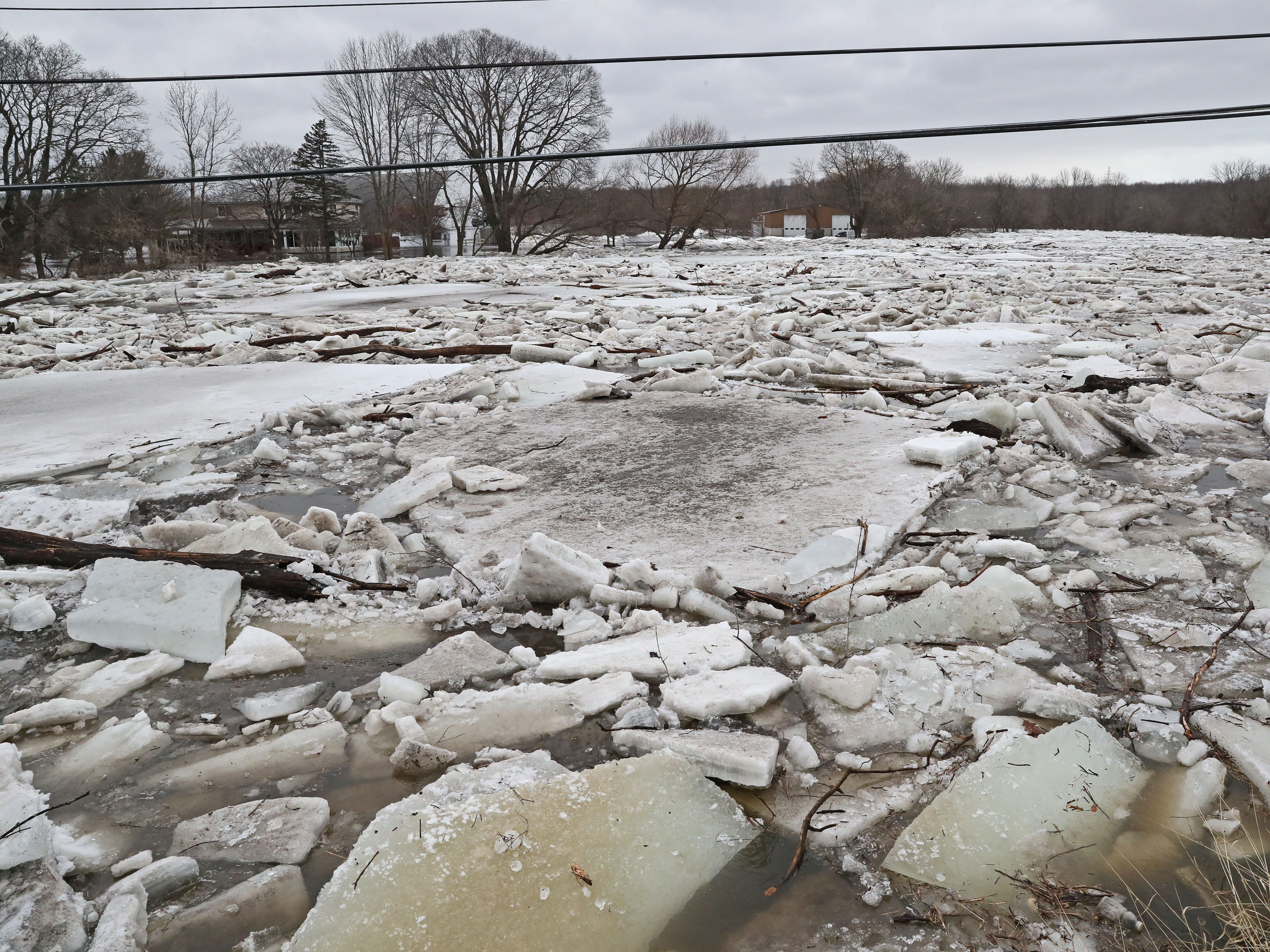Ice on the Milwaukee River looking north from that location. March 15, 2019 Grafton firefighters rescued two people from the Riverview Kennel on the Milwaukee River at  1584 Pioneer Rd in Cedarburg.  Ice going out on the river was blocked by bridge diverting flow over the Cty Highway C and the surround low areas.