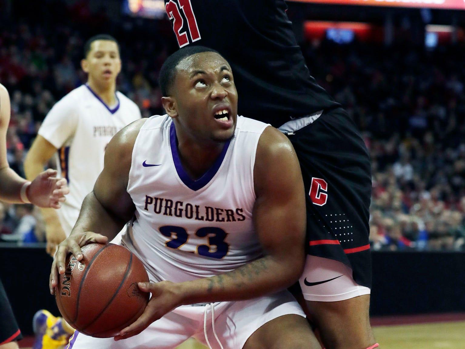 Milwaukee Washington's Johntae Martin tries to find space under the basket,
