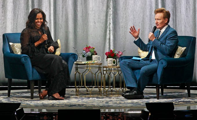 "Former first lady Michelle Obama and Conan O'Brien, enjoy a moment during her Milwaukee book tour,  ""Becoming: A Conversation with Michelle Obama""  at the Miller High Life Theatre."