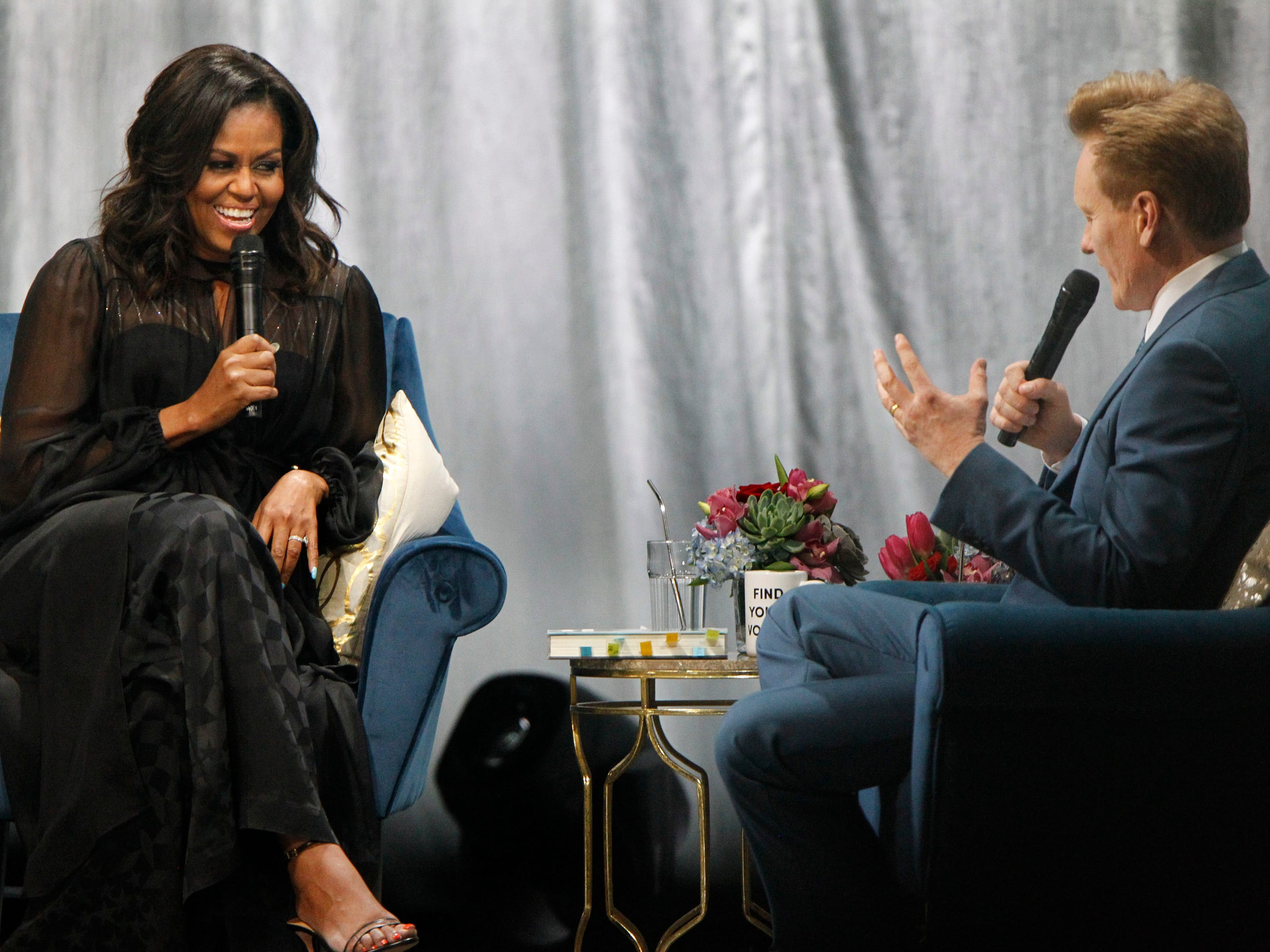 "Former first lady Michelle Obama enjoys a light moment with Conan O'Brien during her ""Becoming: A Conversation with Michelle Obama"" at the Miller High Life Theatre on Thursday night."