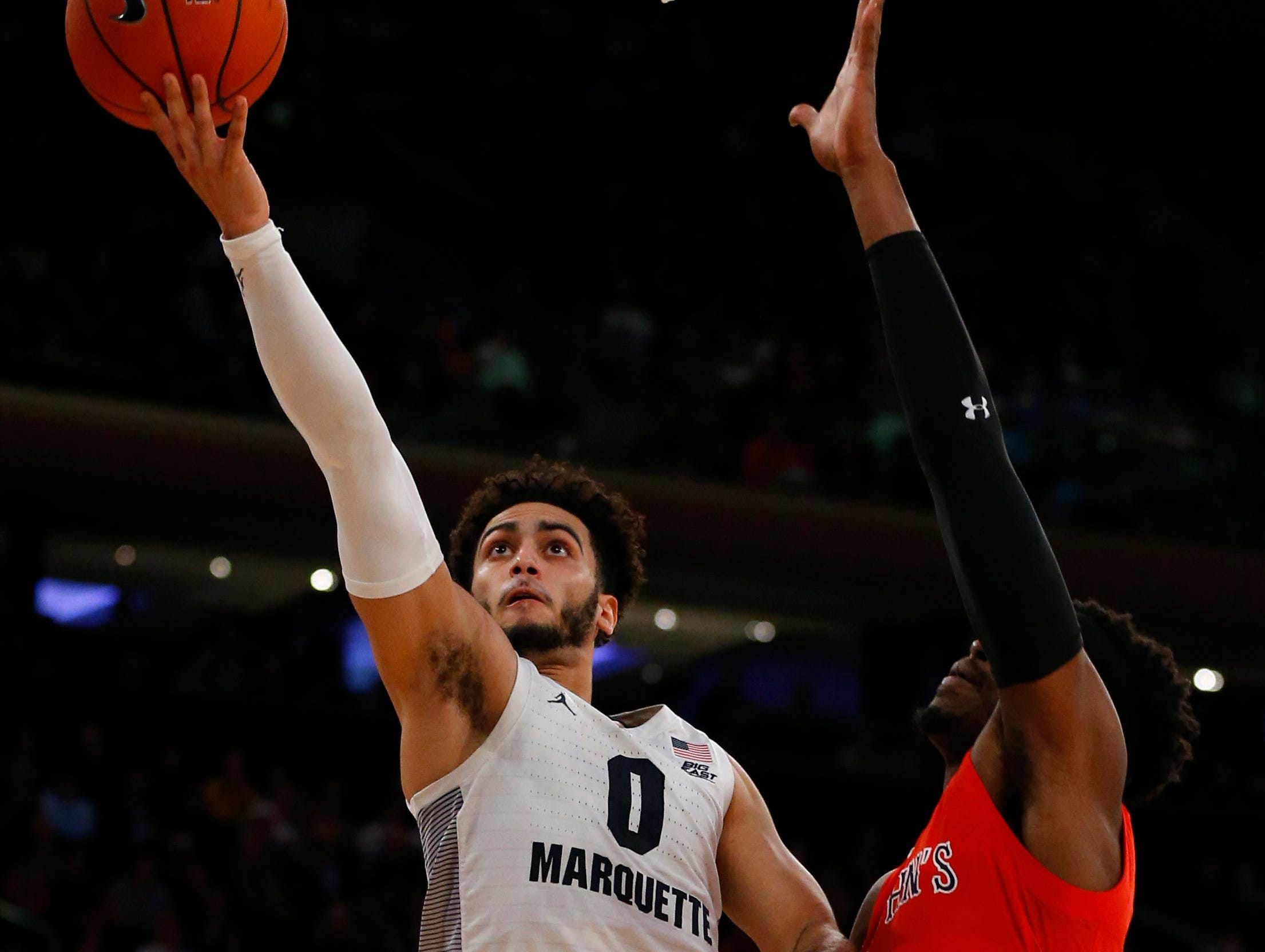 Marquette's Markus Howard gets past Sedee Keita of St. John's on his way to the basket.