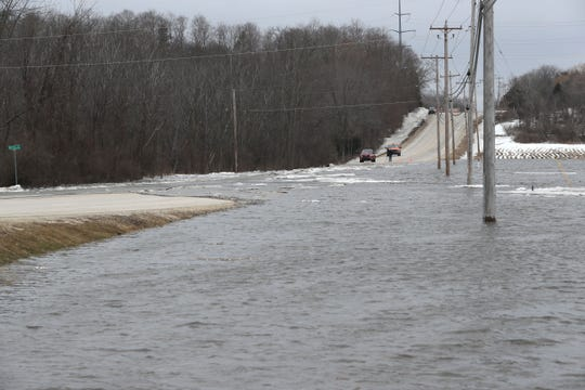Water from the Milwaukee River flows across County Road C, near the Riverview Kennel on Friday.
