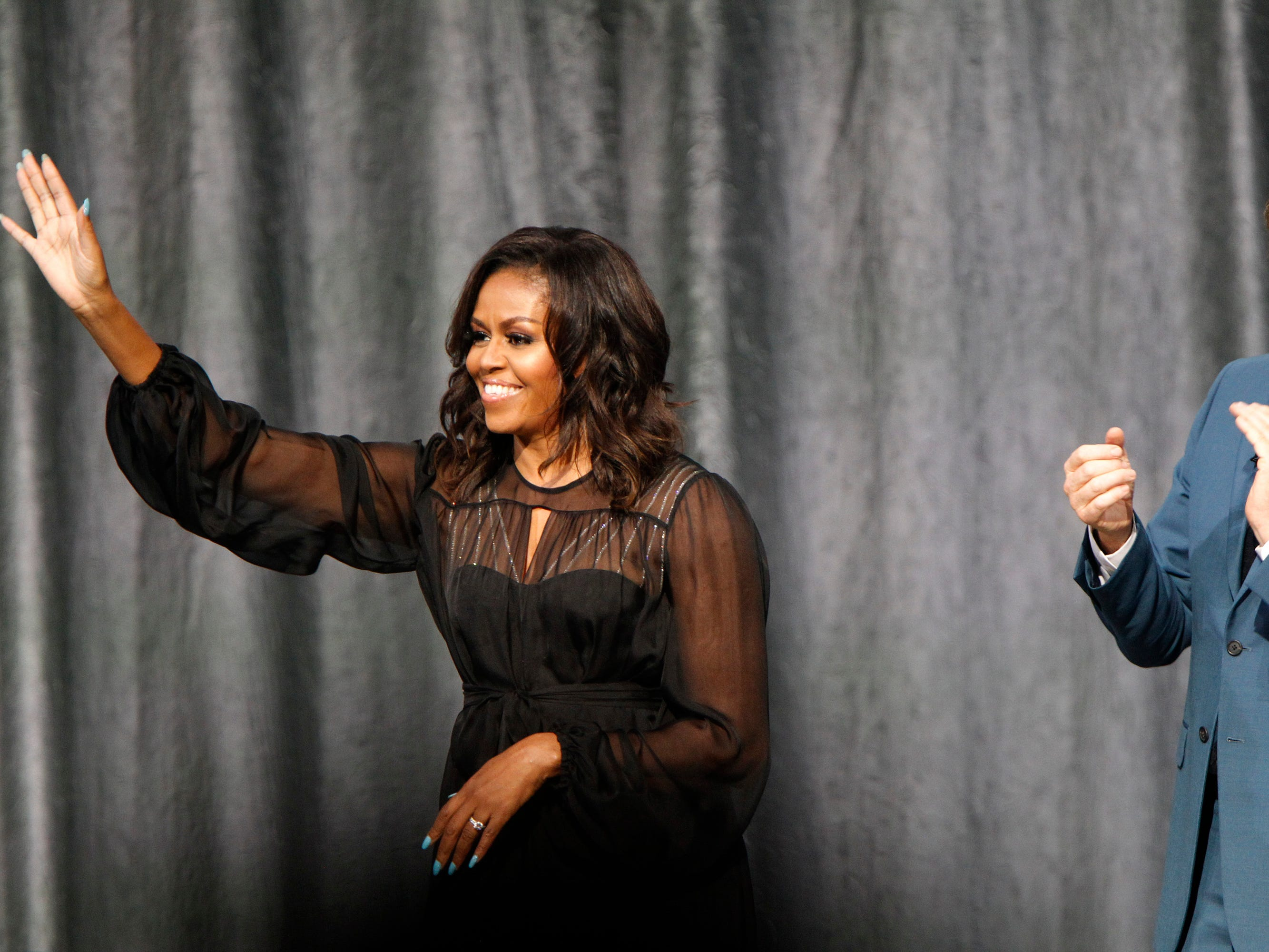 "Former first lady Michelle Obama greets the audience as she arrives on stage for ""Becoming: A Conversation with Michelle Obama"" at the Miller High Life Theatre on Thursday. Comedian Conan O'Brien, right, was the moderator for the event."