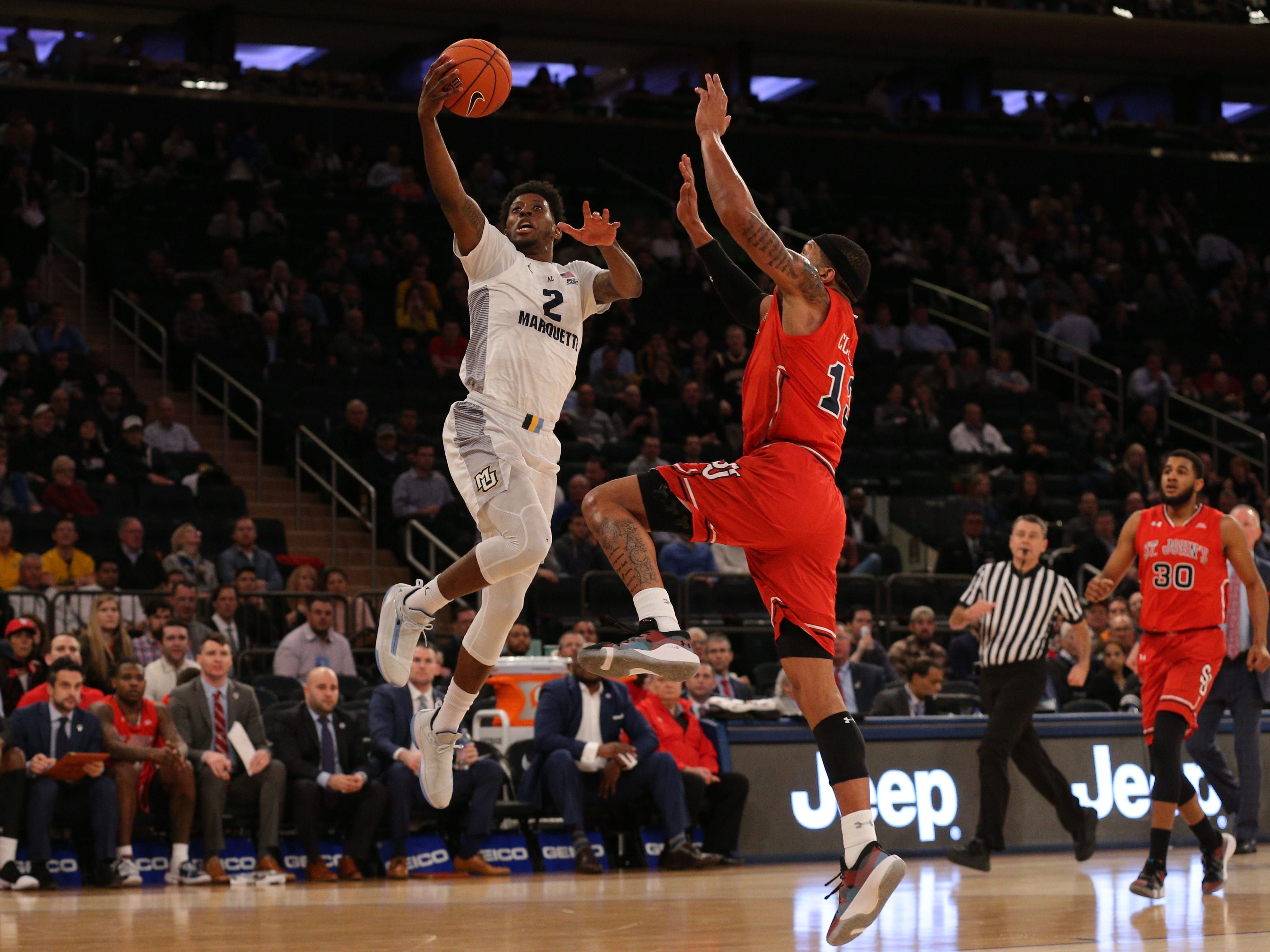 Marquette guard Sacar Anim beats St. John's forward Marvin Clark to the basket.
