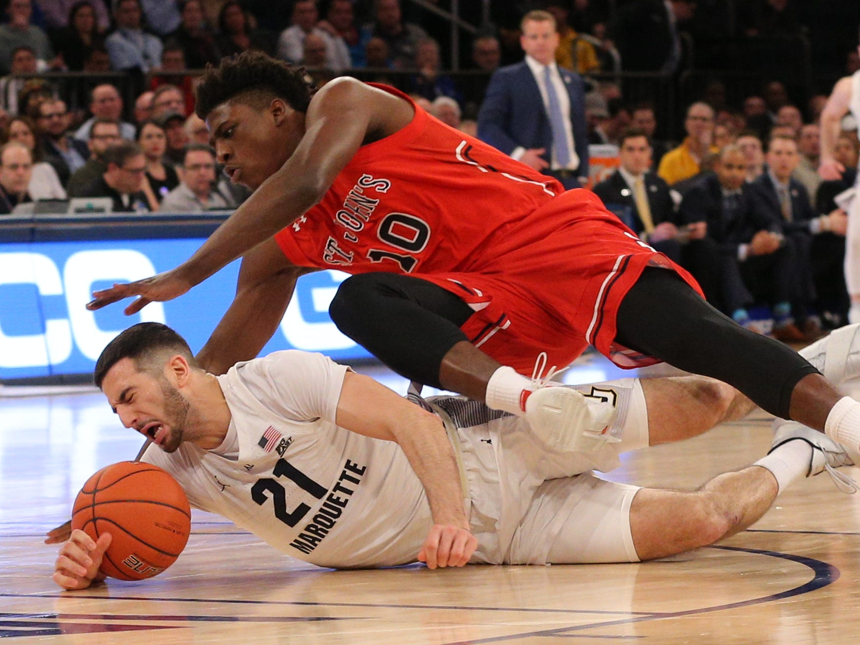 Marquette's Joseph Chartouny and St. John's Marcellus Earlington go after a loose ball.