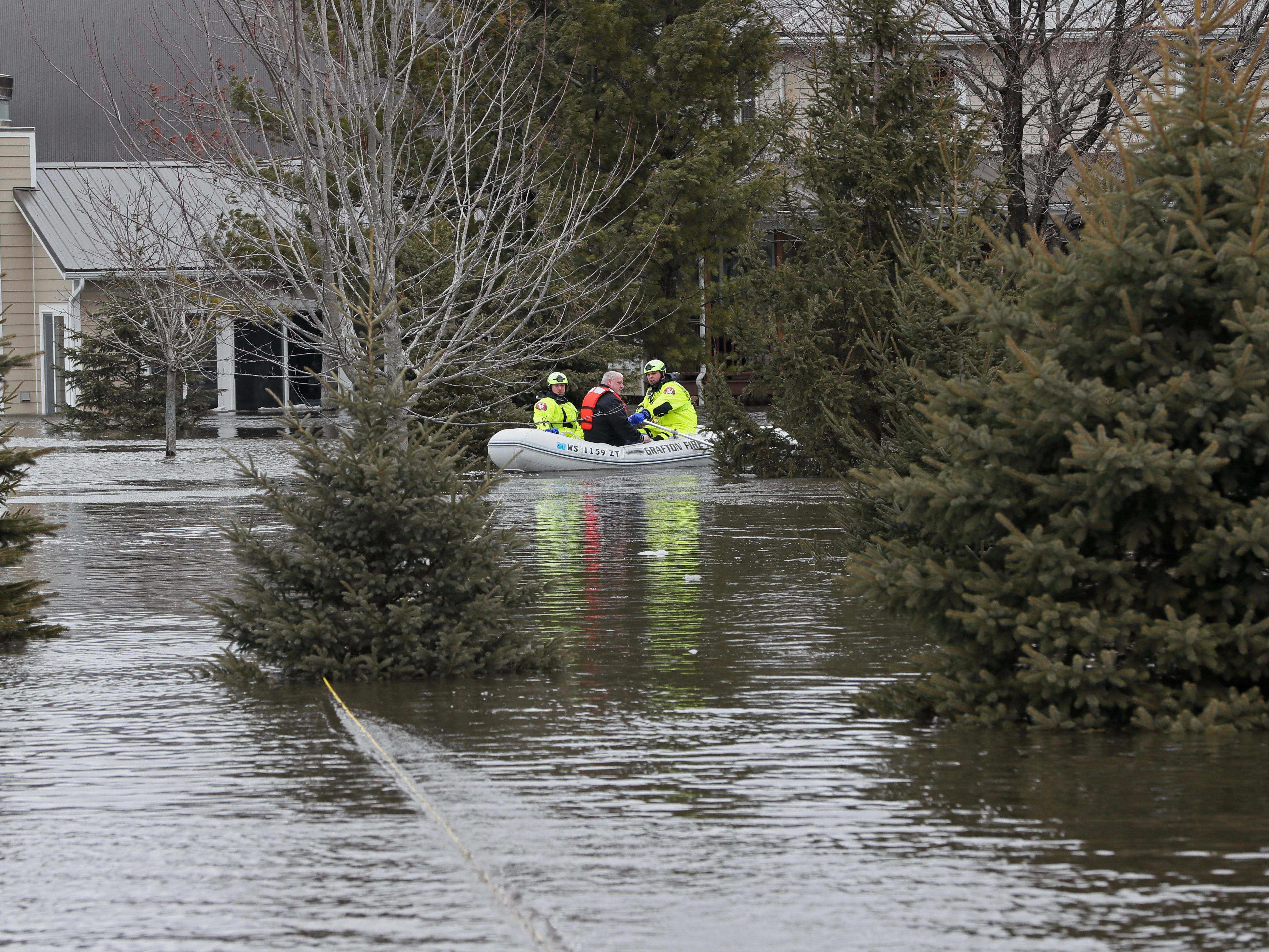 Grafton firefighters bring a man to high ground the rescued from the home at rear. March 15, 2019 Grafton firefighters rescued two people from the Riverview Kennel on the Milwaukee River at  1584 Pioneer Rd in Cedarburg.  Ice going out on the river was blocked by bridge diverting flow over the Cty Highway C and the surround low areas.