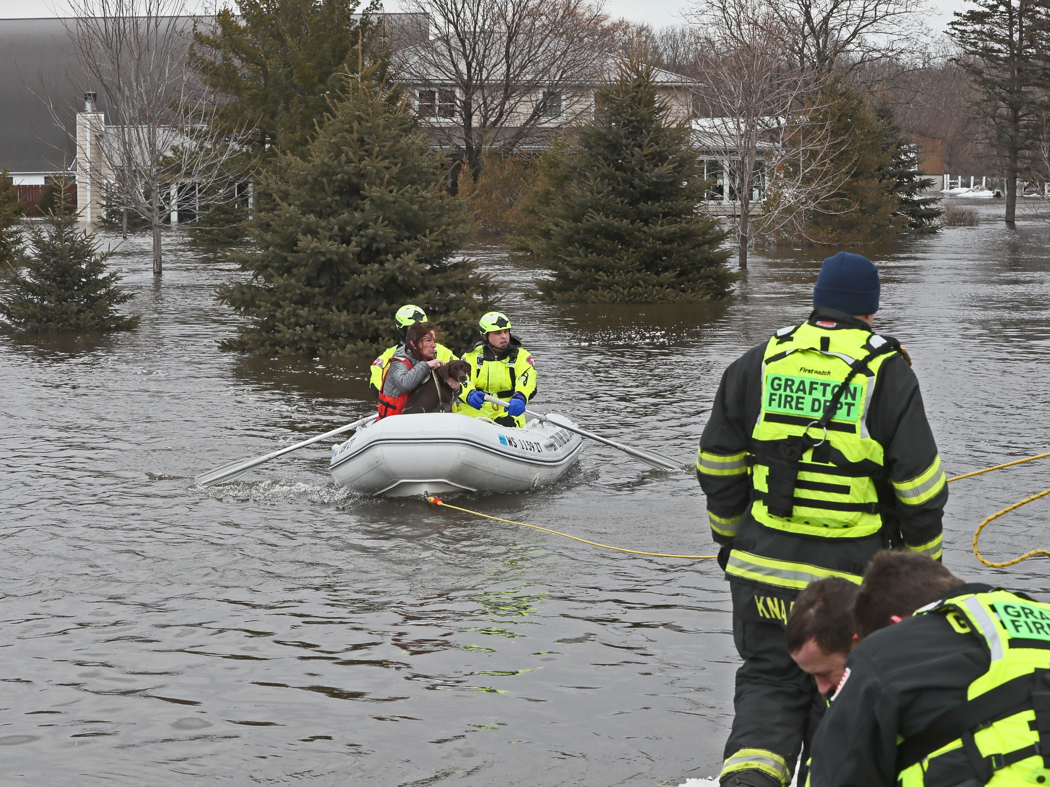 A woman and her dog are rescued from the home at rear. March 15, 2019 Grafton firefighters rescued two people from the Riverview Kennel on the Milwaukee River at  1584 Pioneer Rd in Cedarburg.  Ice going out on the river was blocked by bridge diverting flow over the Cty Highway C and the surround low areas.