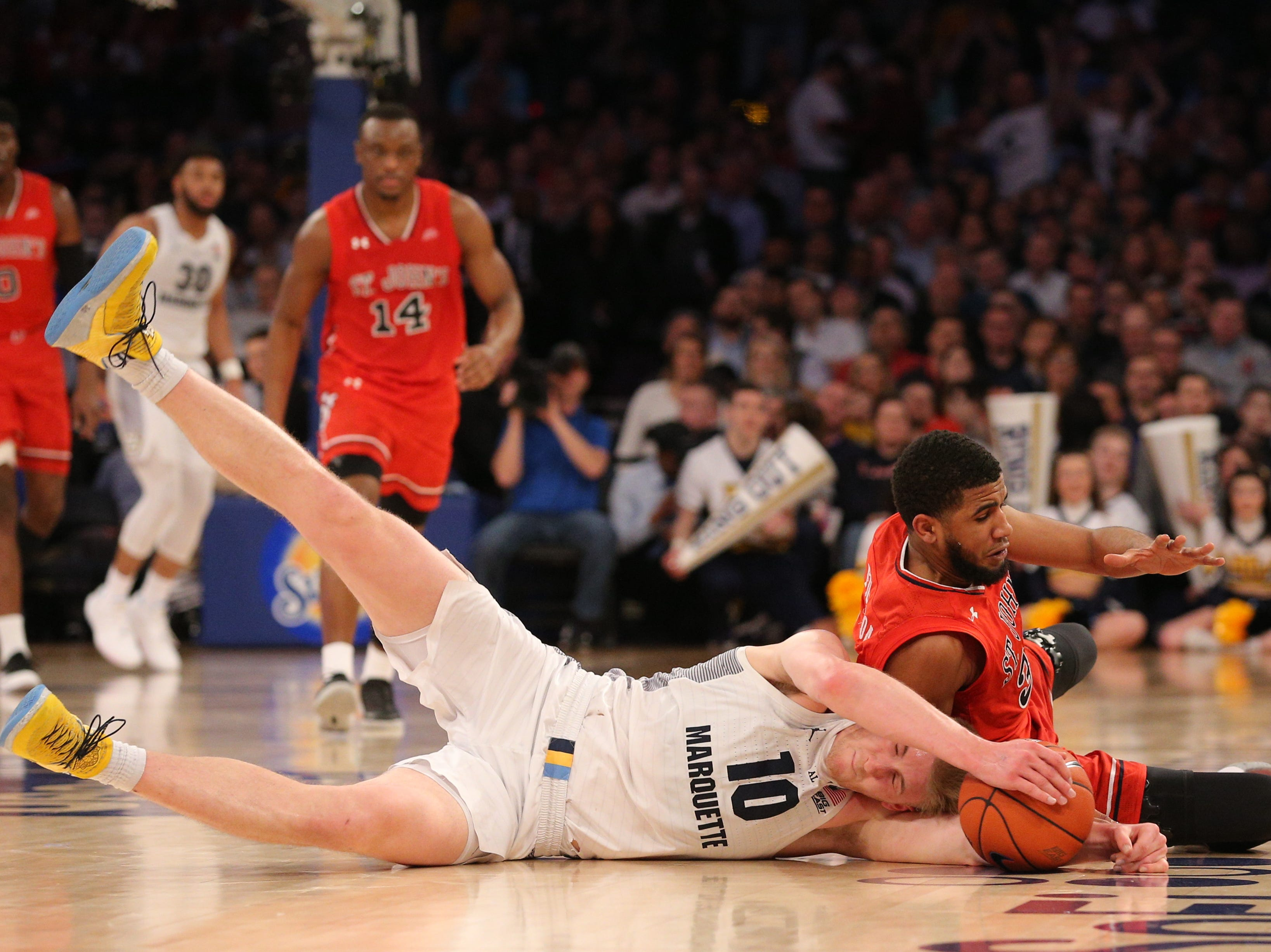 Marquette Golden Eagles guard Sam Hauser  and St. John's Red Storm guard LJ Figueroa go after a loose ball.