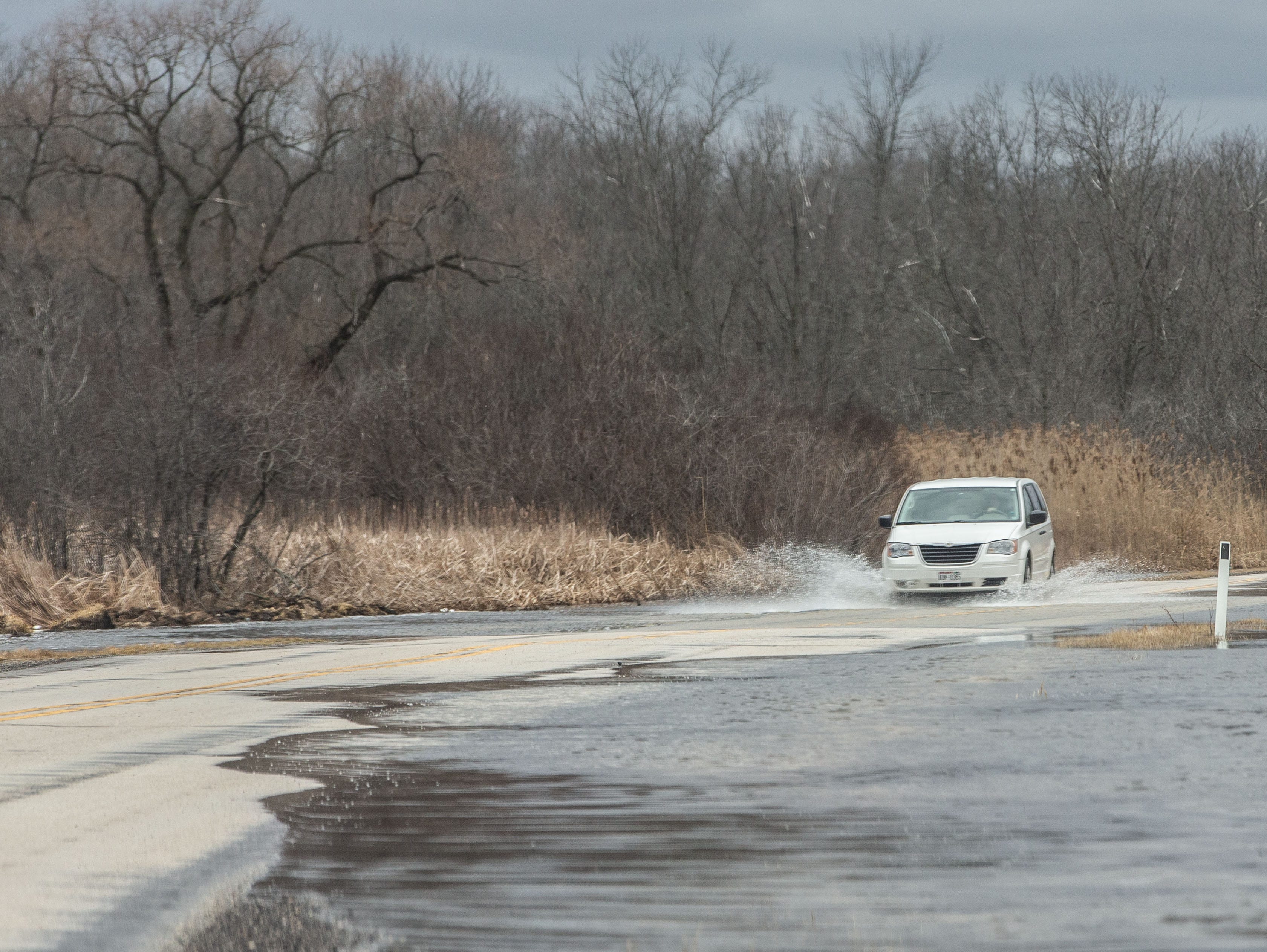 A van drives through flood water on Petersen Road in Hartland on Friday, March 15, 2019. Spring-like temperatures caused flooding across both Washington and Waukesha counties.