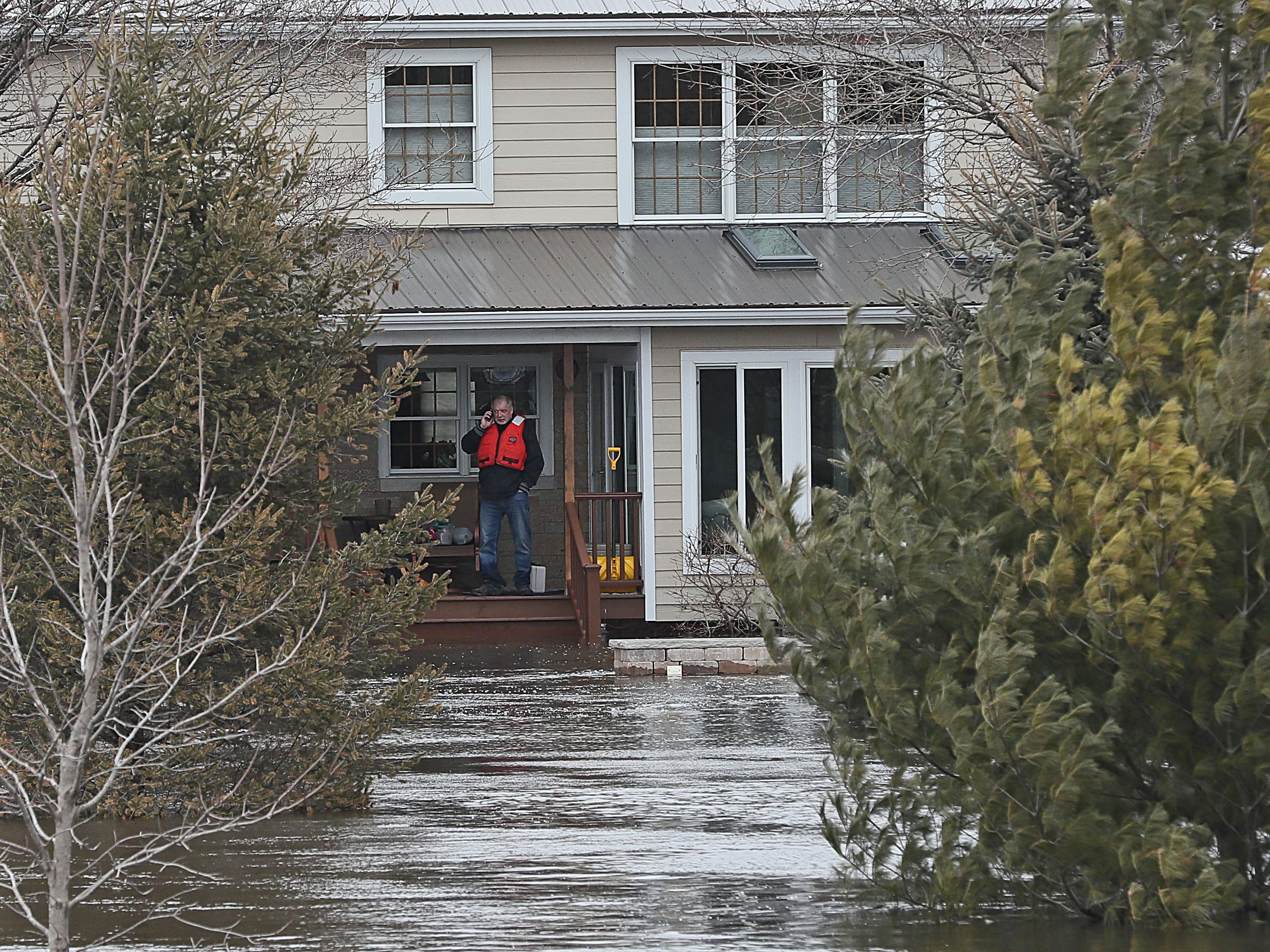One of the home's residents wait for the firefighters boat to take him to high ground. March 15, 2019 Grafton firefighters rescued two people from the Riverview Kennel on the Milwaukee River at  1584 Pioneer Rd in Cedarburg.  Ice going out on the river was blocked by bridge diverting flow over the Cty Highway C and the surround low areas.