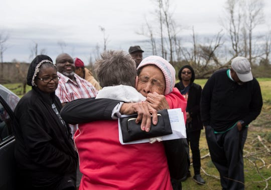 Neighbors Beverly Guerin, left, and Arcuqila Pearson hug in front of Pearson's tornado damaged house in Titus, Ala., on Friday, March 15, 2019.