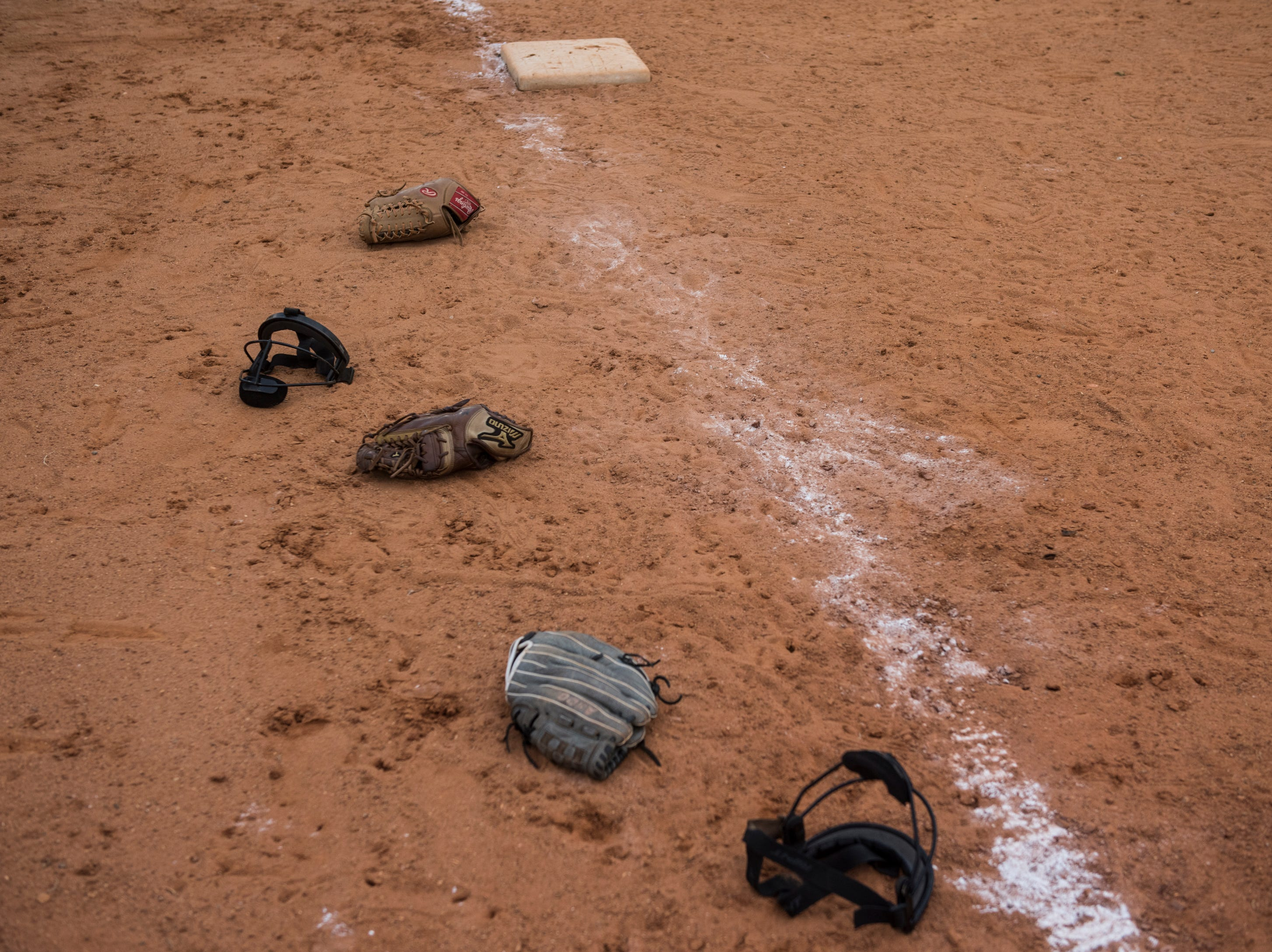 Gloves and helmets lay on the ground after Brew Tech hosted Tallassee after the game at Thompson Park in Montgomery, Ala., on Thursday, March 14, 2019. Tallassee defeated Brew Tech 7-0.