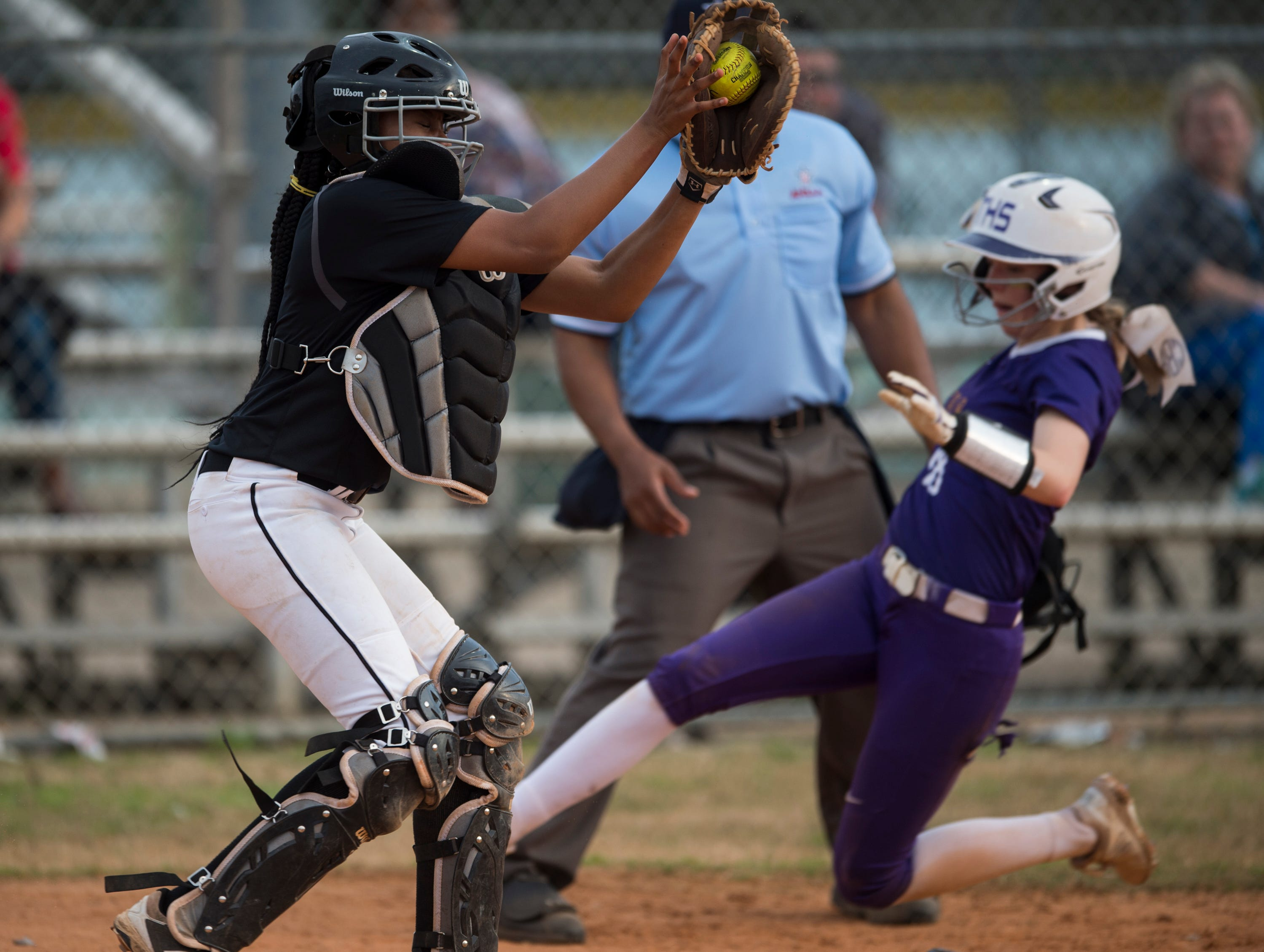 Tallassee's Chloe Baynes (18) slides safely into home plate past Brew Tech's Airele Anderson (9) at Thompson Park in Montgomery, Ala., on Thursday, March 14, 2019. Tallassee defeated Brew Tech 7-0.