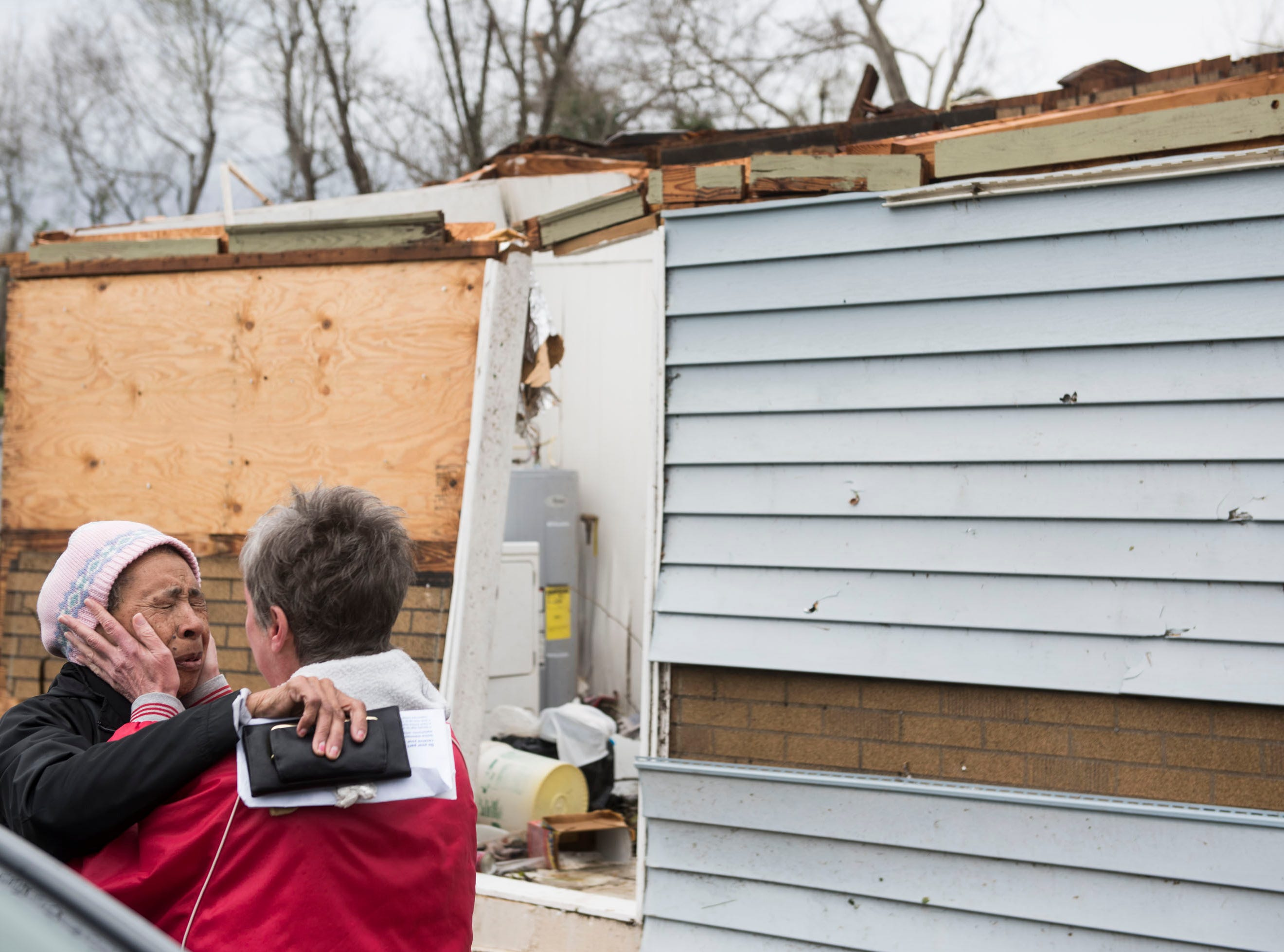 Neighbors Arcuqila Pearson, left, and Beverly Guerin hug in front of Pearson's tornado damaged house in Titus, Ala., on Friday, March 15, 2019.