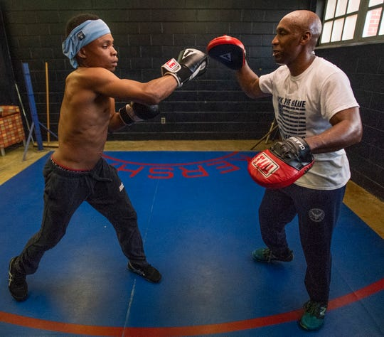 Montgomery Police Lt. John Mackey, right, teaches Tycorian Stephens boxing at the McIntyre Community Center in Montgomery, Ala., on Thursday March 14, 2019.