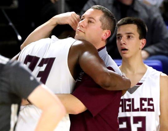 Eagleville's head coach Davy McClaran hugs senior Eagleville's Demarious Stoudemire (33) as he comes out of the game as they lose to Columbia Academy during the semifinal round of the TSSAA Class A Boys State Tournament, on Thursday, March 15, 2019, at Murphy Center in Murfreesboro, Tenn.