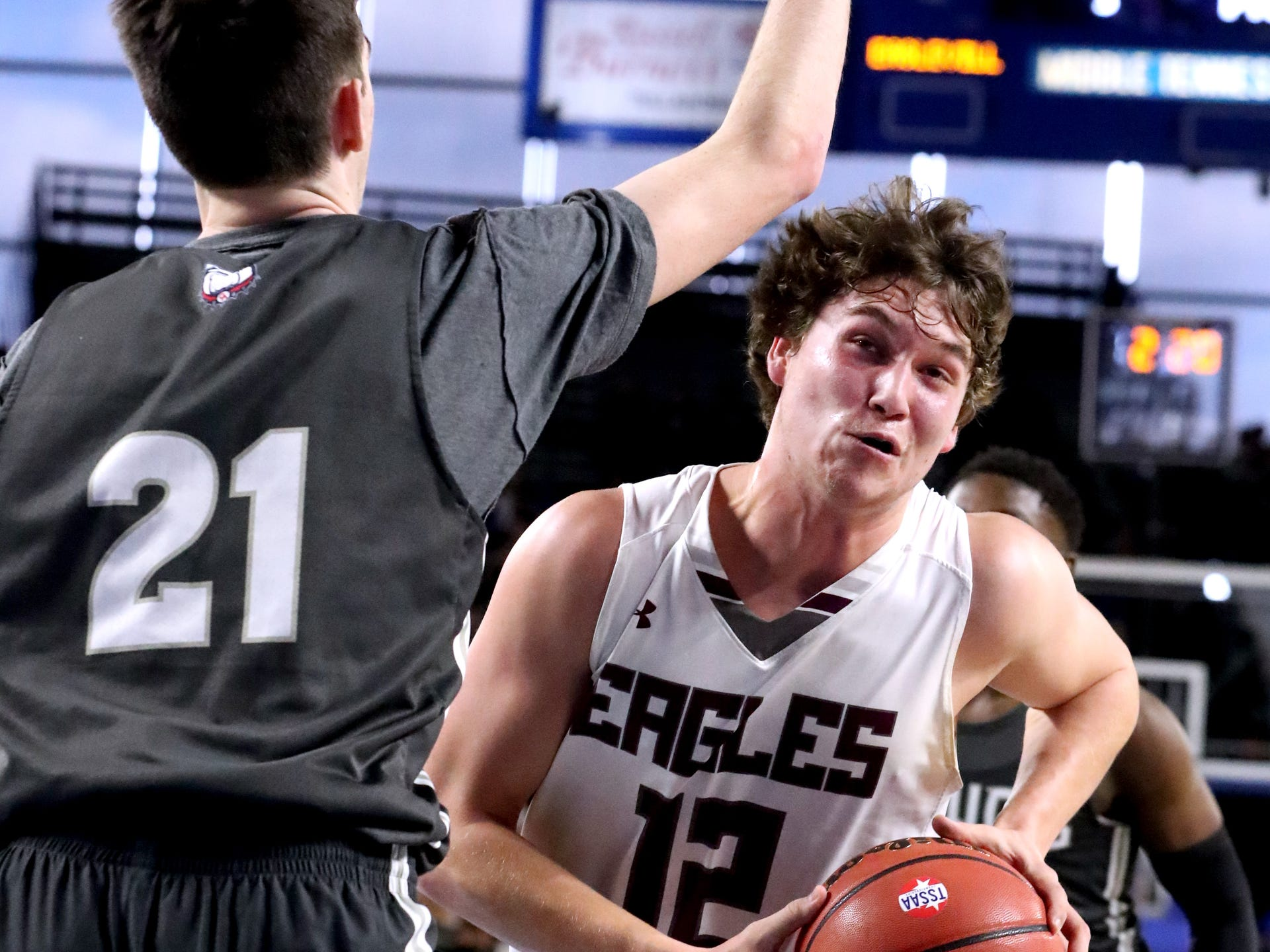 Eagleville's Ethan Cobb (12) drives to the basket as Columbia Academy's Eli Hyle (21) guards him during the semifinal round of the TSSAA Class A Boys State Tournament, on Thursday, March 15, 2019, at Murphy Center in Murfreesboro, Tenn.