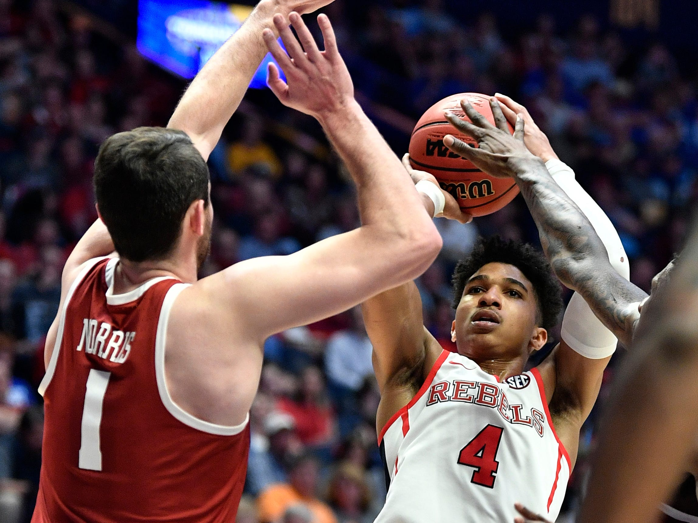 Ole Miss guard Breein Tyree (4) shoots defeded by Alabama guard/forward Riley Norris (1) during the second half of the SEC Men's Basketball Tournament game at Bridgestone Arena in Nashville, Tenn., Thursday, March 14, 2019.
