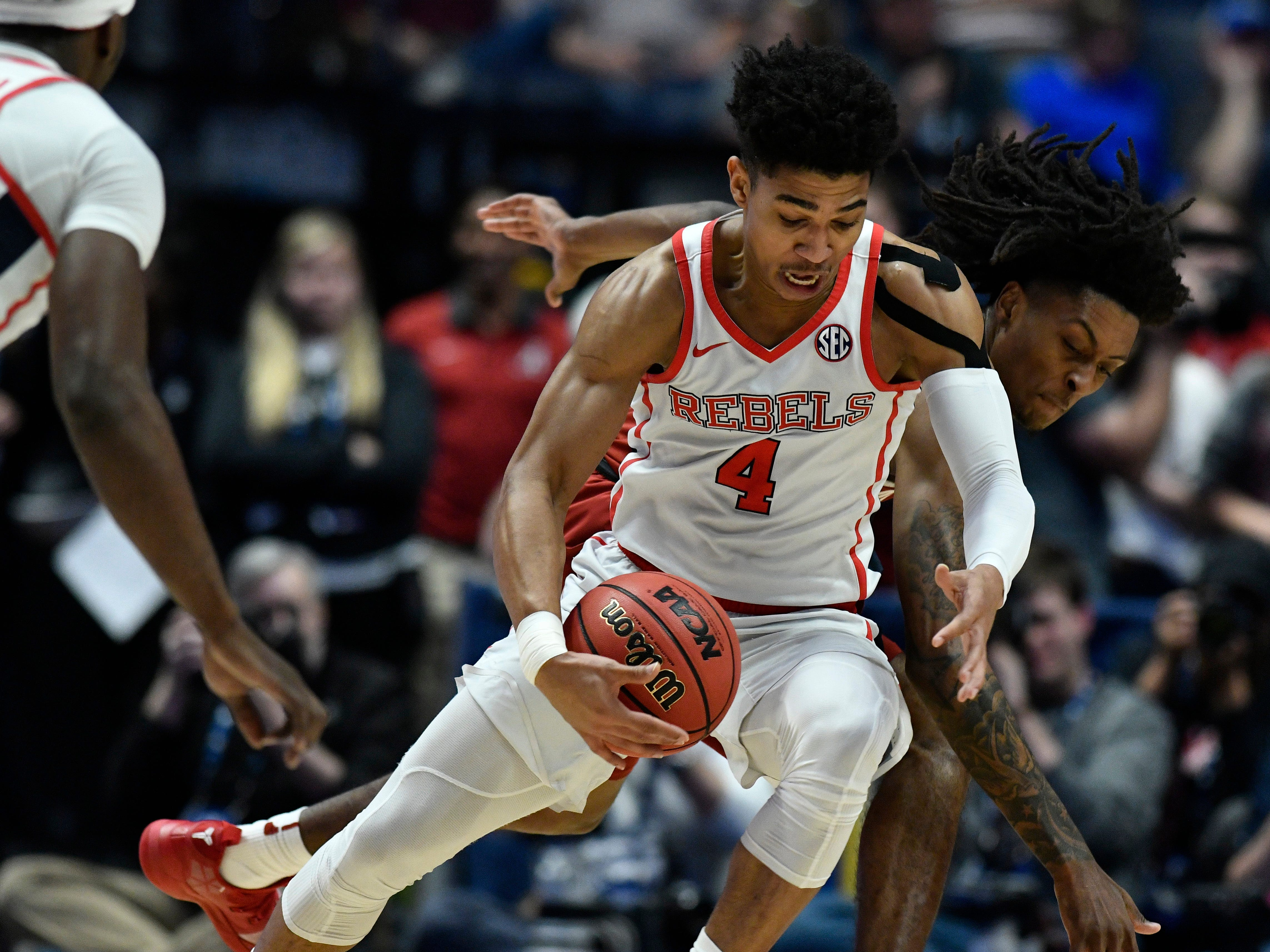 Ole Miss guard Breein Tyree (4) moves the ball defended by Alabama guard John Petty (23) during the first half of the SEC Men's Basketball Tournament game at Bridgestone Arena in Nashville, Tenn., Thursday, March 14, 2019.