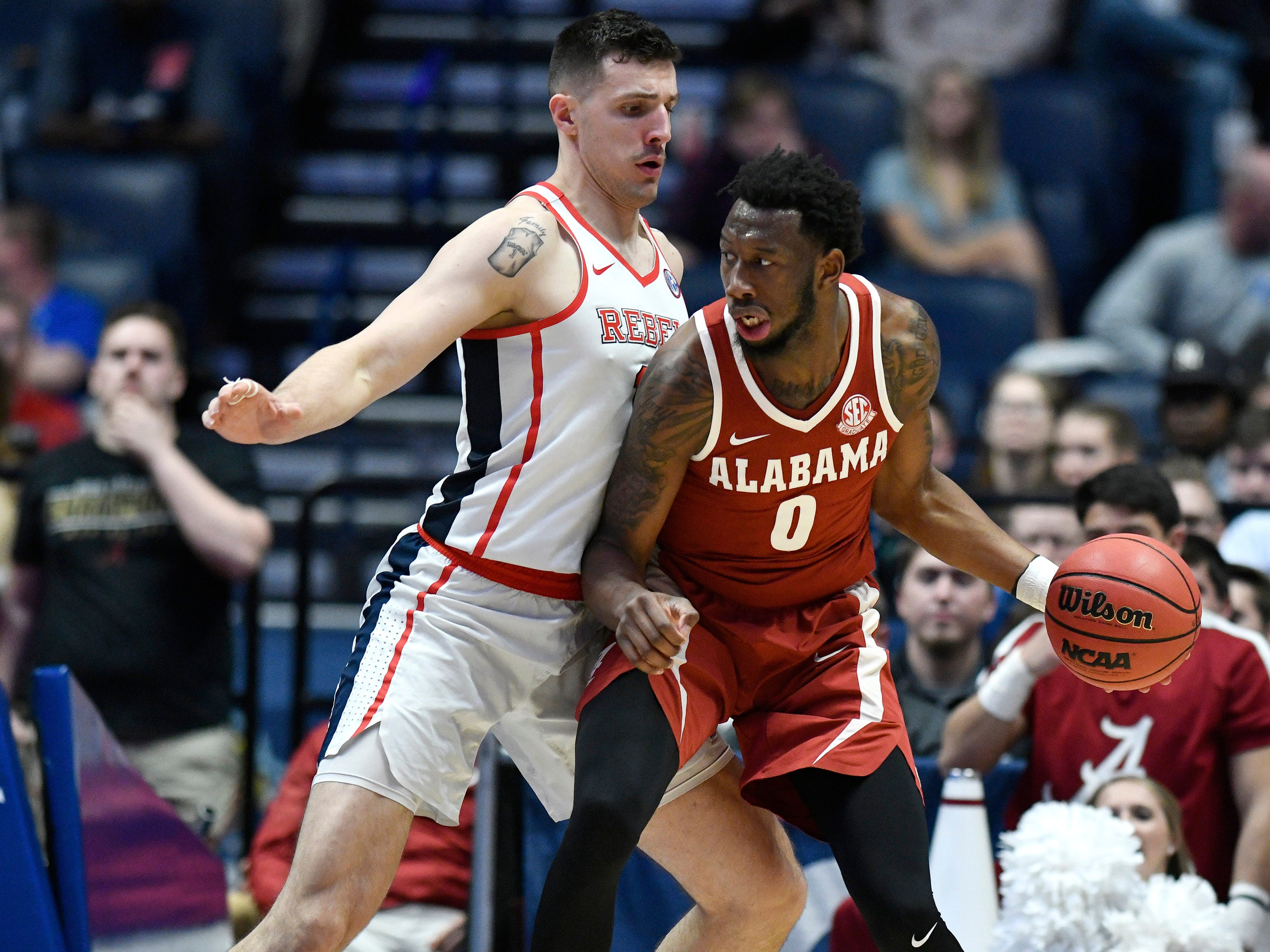 Alabama forward Donta Hall (0) moves the ball defended by Ole Miss center Dominik Olejniczak (13) during the second half of the SEC Men's Basketball Tournament game at Bridgestone Arena in Nashville, Tenn., Thursday, March 14, 2019.