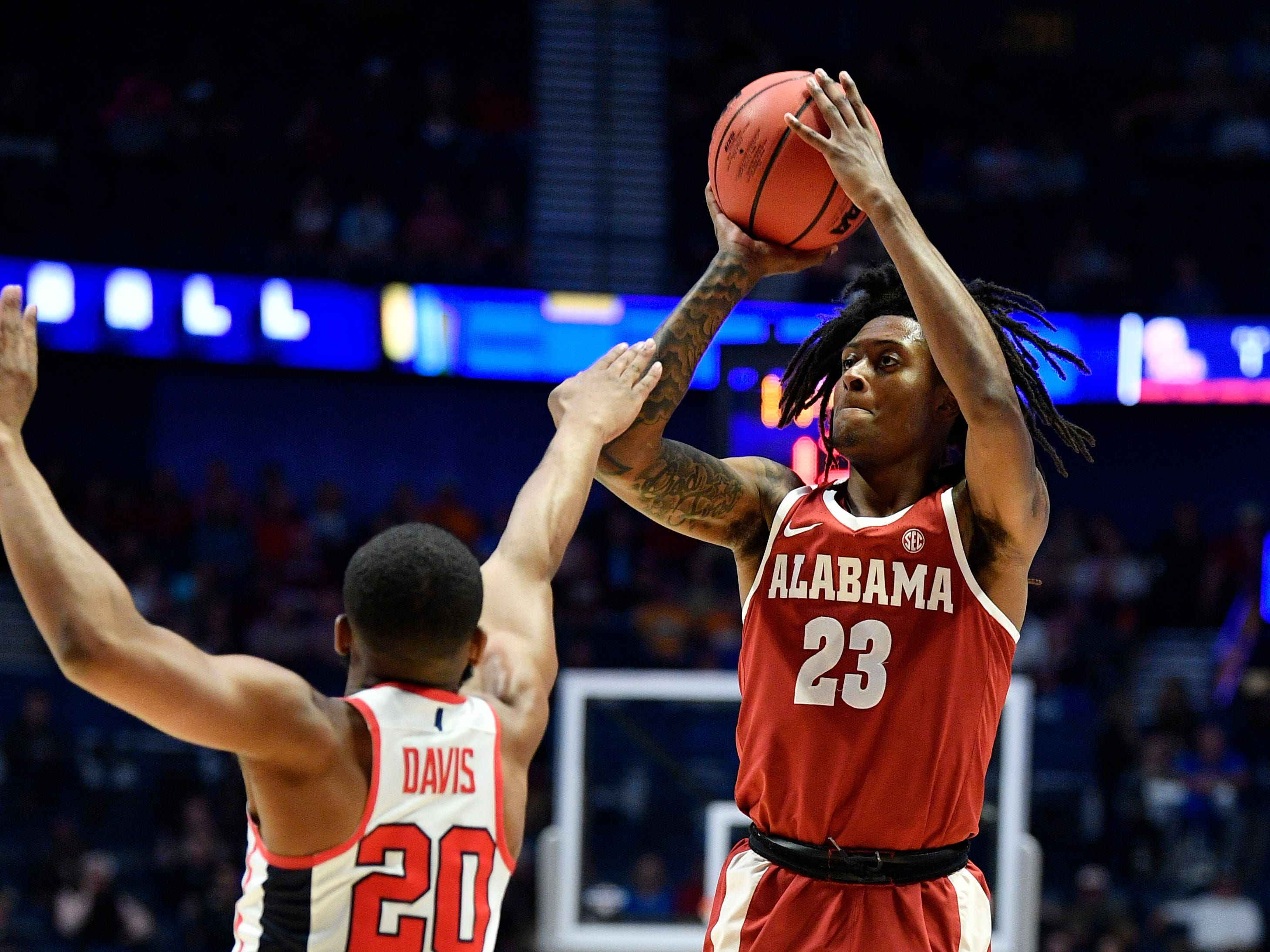 Alabama guard John Petty (23) takes a shot defended by Ole Miss guard D.C. Davis (20) during the first half of the SEC Men's Basketball Tournament game at Bridgestone Arena in Nashville, Tenn., Thursday, March 14, 2019.