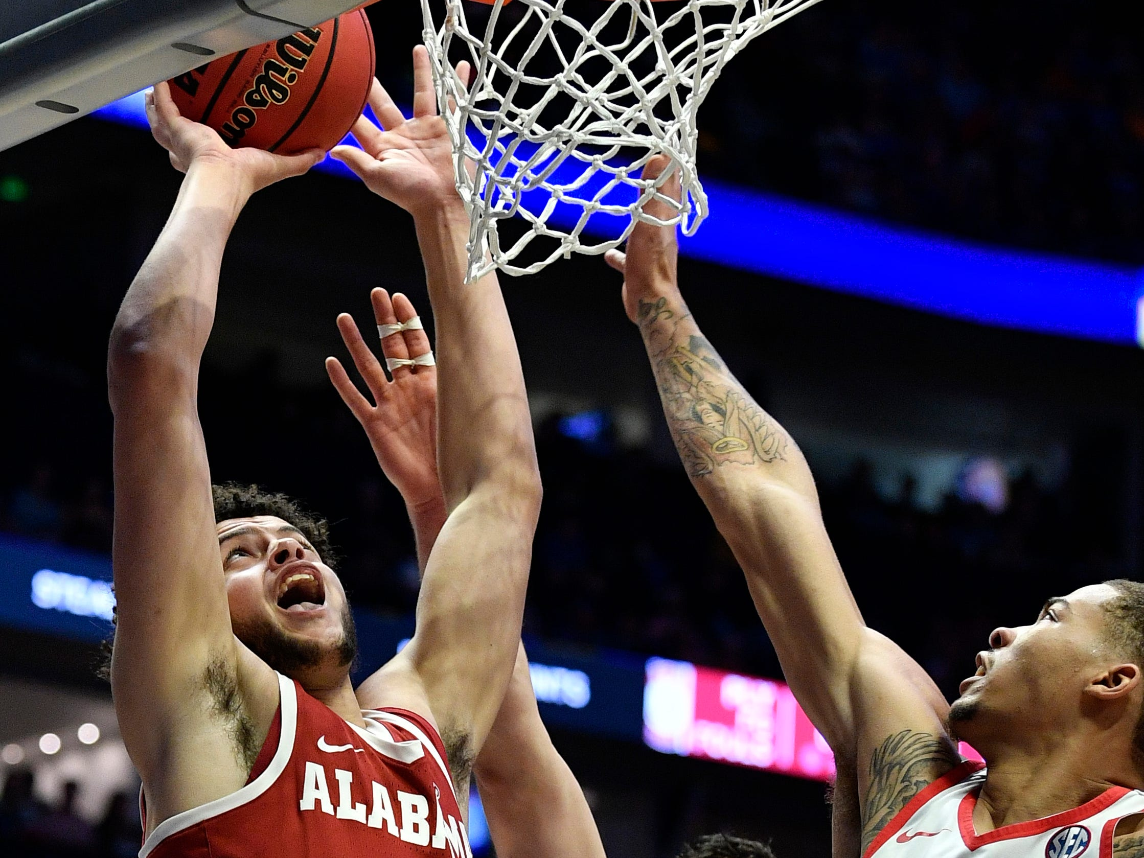 Alabama forward Alex Reese (3) goes up for a shot defended by Ole Miss center Dominik Olejniczak (13) and forward KJ Buffen (14) during the first half of the SEC Men's Basketball Tournament game at Bridgestone Arena in Nashville, Tenn., Thursday, March 14, 2019.