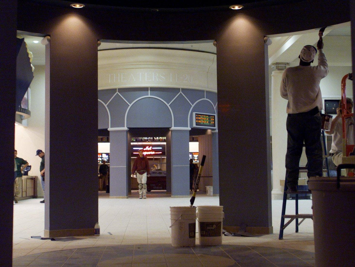 Painter Calvin Heard puts the finishing touches on an entryway at the new Carmike Thoroughbred 20 movie theater in Cool Springs in 1996. ERIC PARSONS