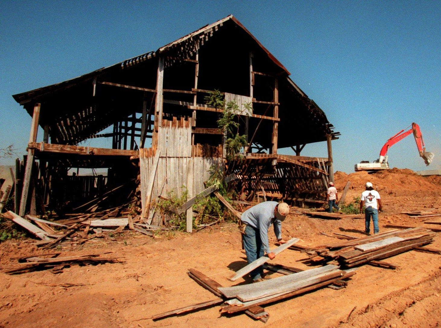 While bulldozers move dirt for a new development in Cool Springs, Juan Gutierrez of RP Industries and other workers take down a barn board in 1996 by board on Thursday. The wood will be reused for a cabin in Knoxville.