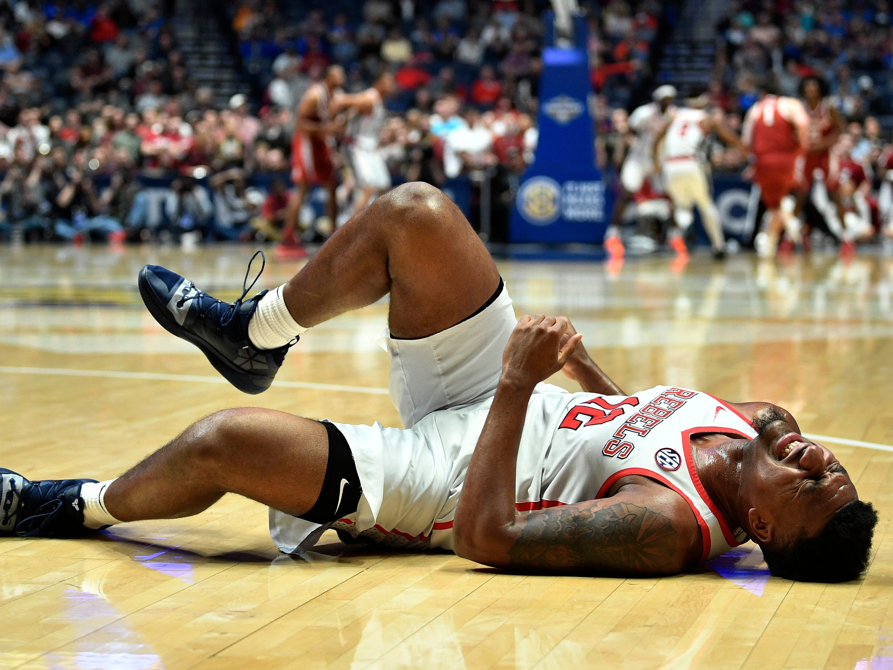 Ole Miss forward Bruce Stevens (12) falls to the court with an injury during the second half of the SEC Men's Basketball Tournament game against Alabama at Bridgestone Arena in Nashville, Tenn., Thursday, March 14, 2019. He later returned to the game.