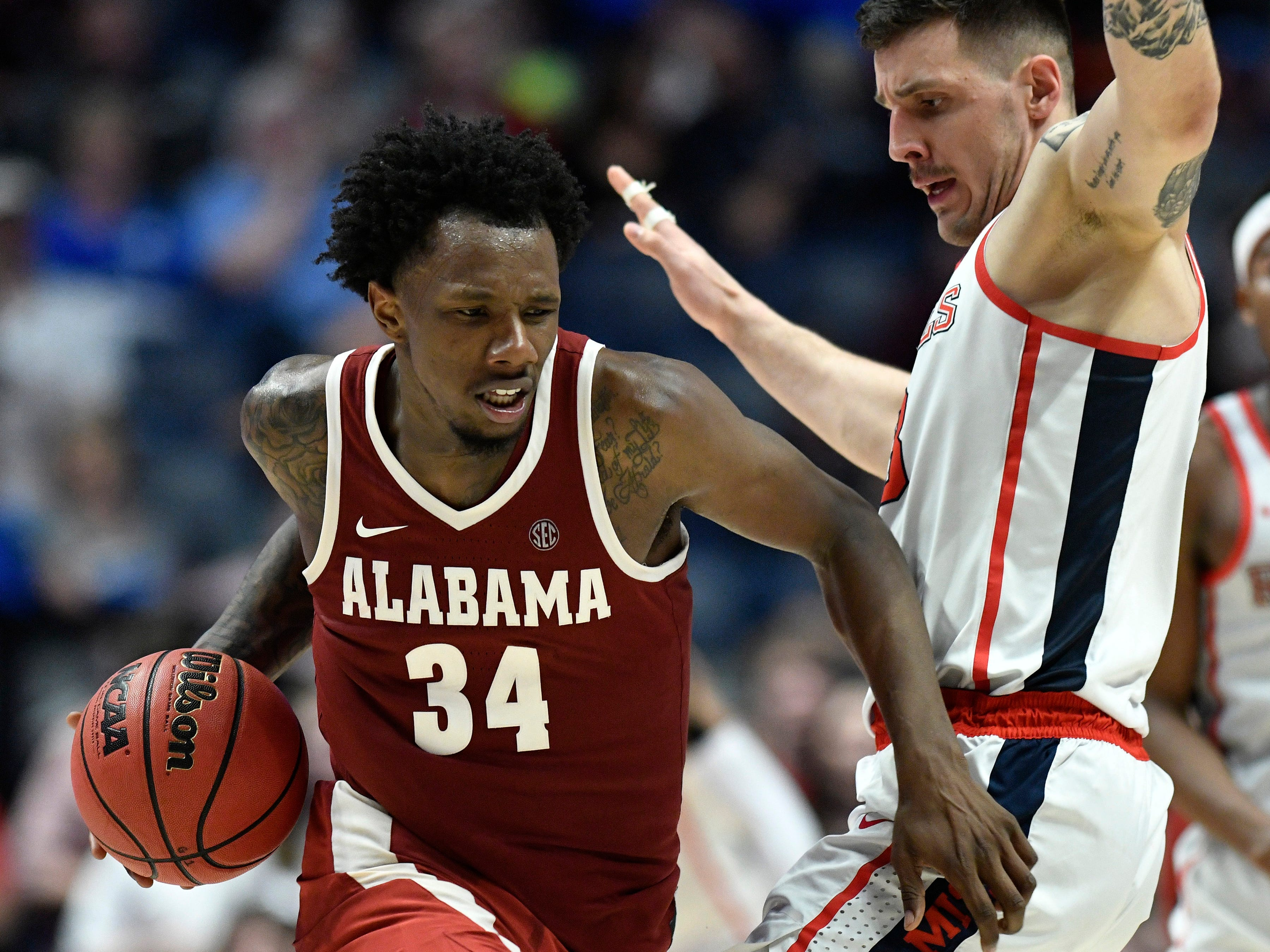 Alabama guard Tevin Mack (34) moves the ball defended by Ole Miss center Dominik Olejniczak (13) during the second half of the SEC Men's Basketball Tournament game at Bridgestone Arena in Nashville, Tenn., Thursday, March 14, 2019.