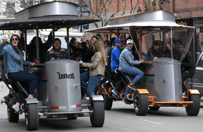 Pedal taverns race each other in downtown Nashville during the SEC Men's Basketball Tournament in Nashville on Friday, March 15, 2019.