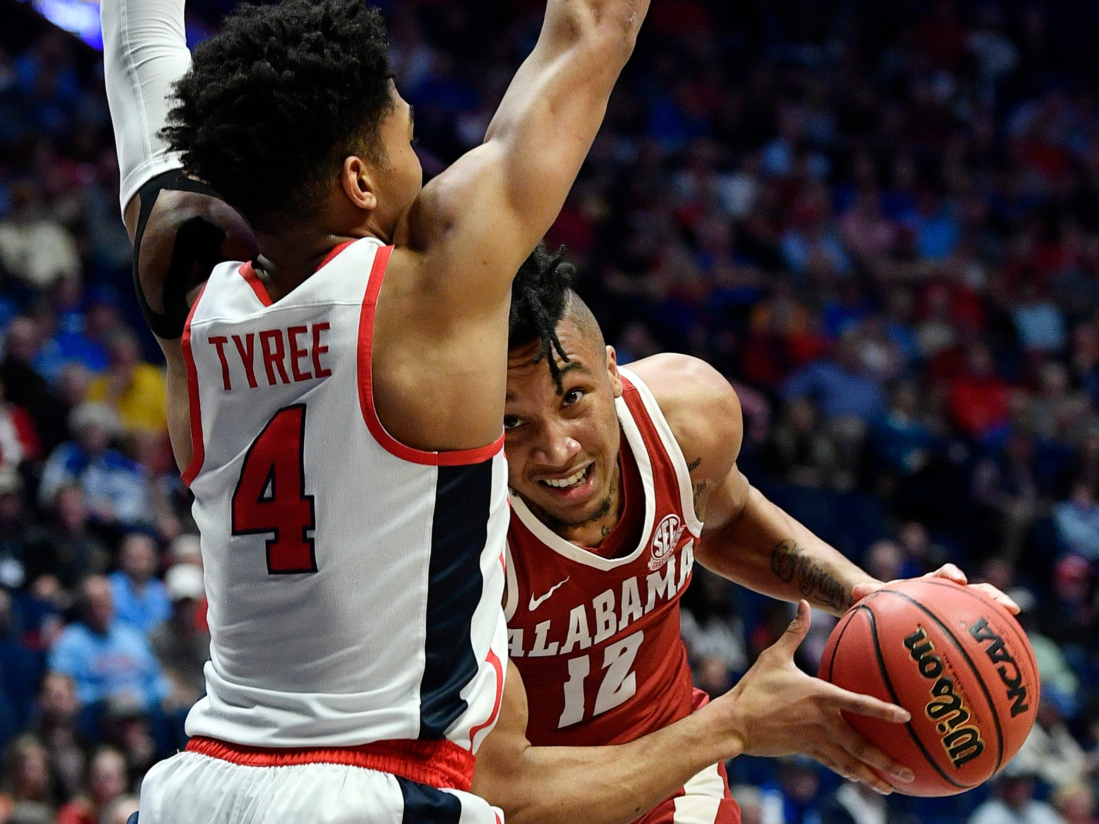 Alabama guard Dazon Ingram (12) tries to move the ball defended by Ole Miss guard Breein Tyree (4) during the first half of the SEC Men's Basketball Tournament game at Bridgestone Arena in Nashville, Tenn., Thursday, March 14, 2019.