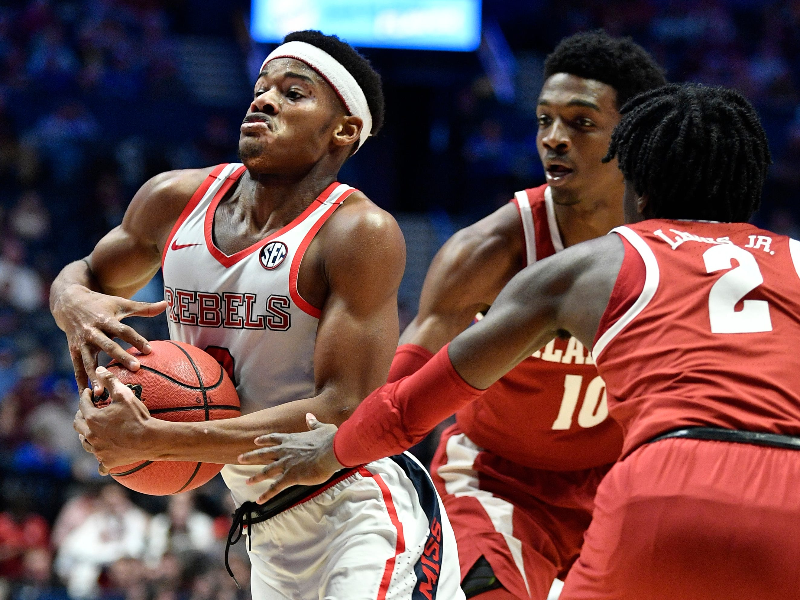 Ole Miss guard Devontae Shuler (2) takes it to the hoop defended by Alabama guards Herbert Jones (10) and Kira Lewis Jr. (2) during the second half of the SEC Men's Basketball Tournament game at Bridgestone Arena in Nashville, Tenn., Thursday, March 14, 2019.