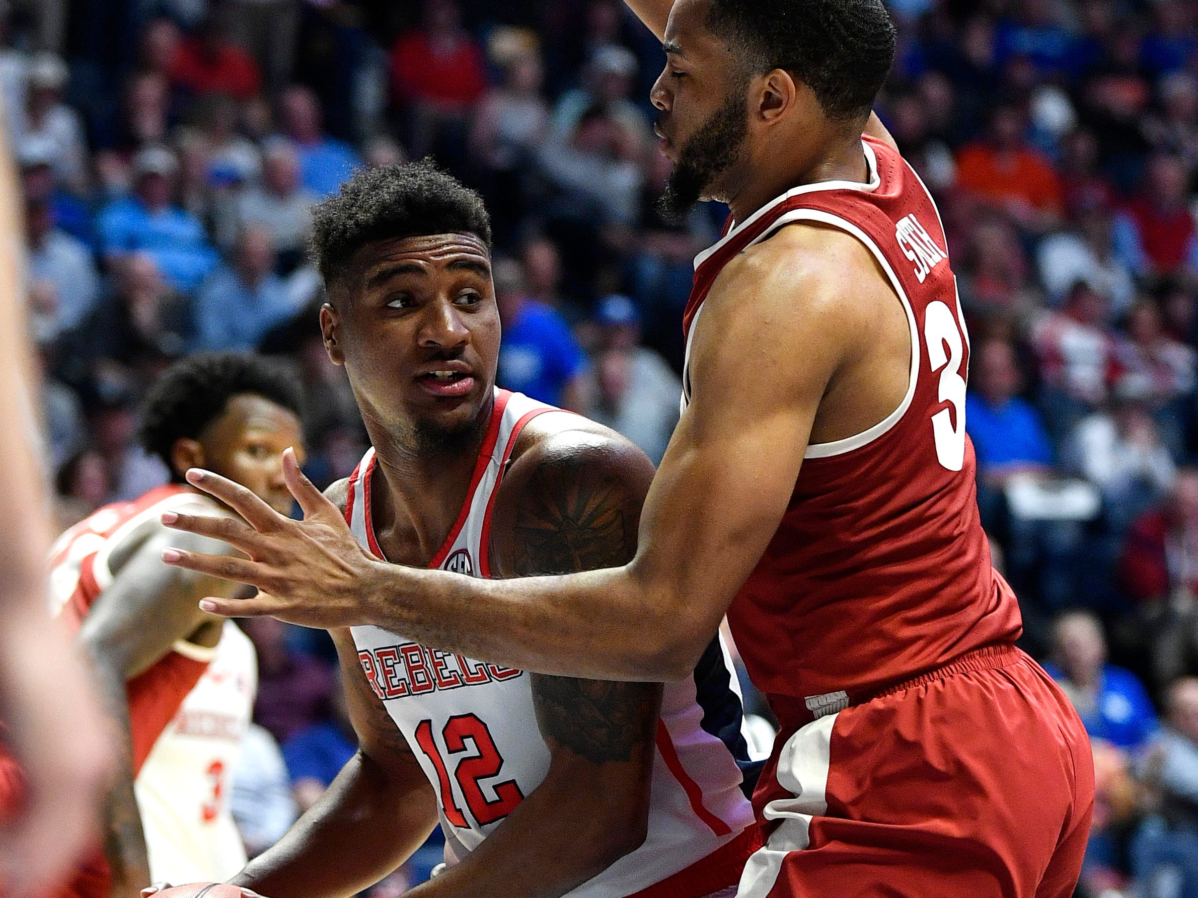 Ole Miss forward Bruce Stevens (12) looks to pass around Alabama forward Galin Smith (30) during the second half of the SEC Men's Basketball Tournament game at Bridgestone Arena in Nashville, Tenn., Thursday, March 14, 2019.
