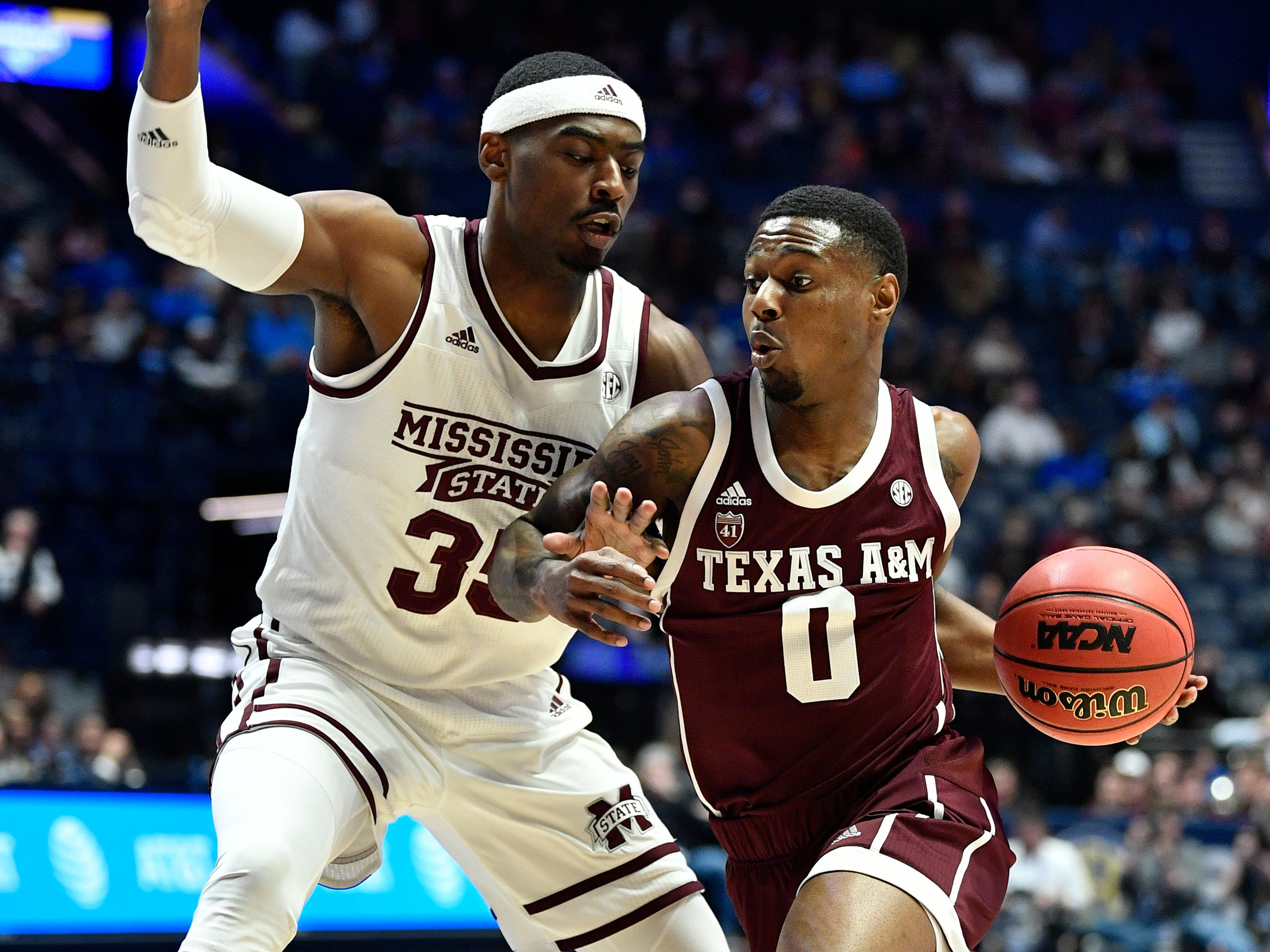 Texas A&M guard Jay Jay Chandler (0) moves the ball defended by Mississippi State forward Aric Holman (35) during the first half of the SEC Men's Basketball Tournament game at Bridgestone Arena in Nashville, Tenn., Thursday, March 14, 2019.