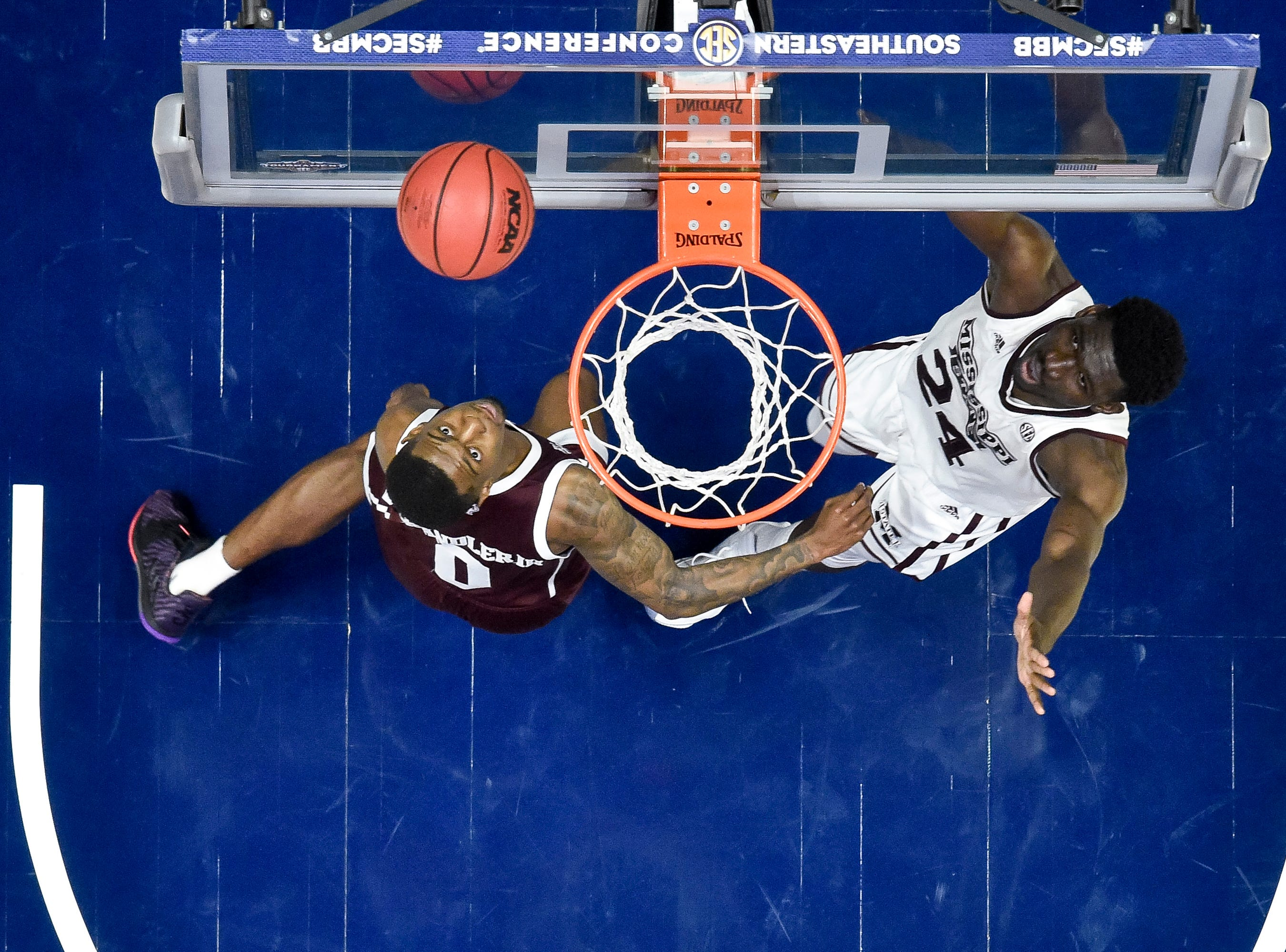 Texas A&M guard Jay Jay Chandler (0) and Mississippi State forward Abdul Ado (24) keep an eye on the ball during the second half of the SEC Men's Basketball Tournament game at Bridgestone Arena in Nashville, Tenn., Thursday, March 14, 2019.