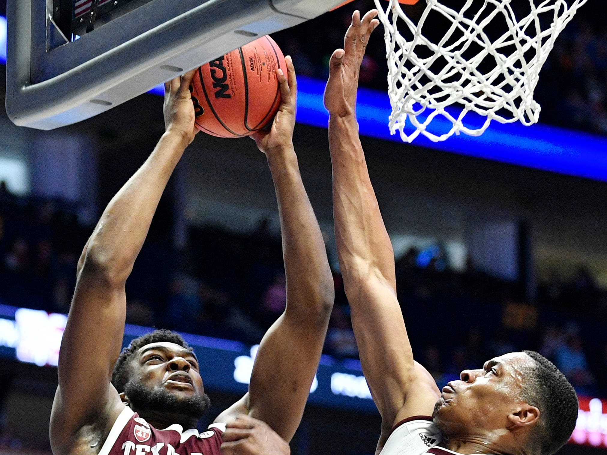 Texas A&M forward Josh Nebo (32) shoots defended by Mississippi State guard Lamar Peters (2) during the first half of the SEC Men's Basketball Tournament game at Bridgestone Arena in Nashville, Tenn., Thursday, March 14, 2019.