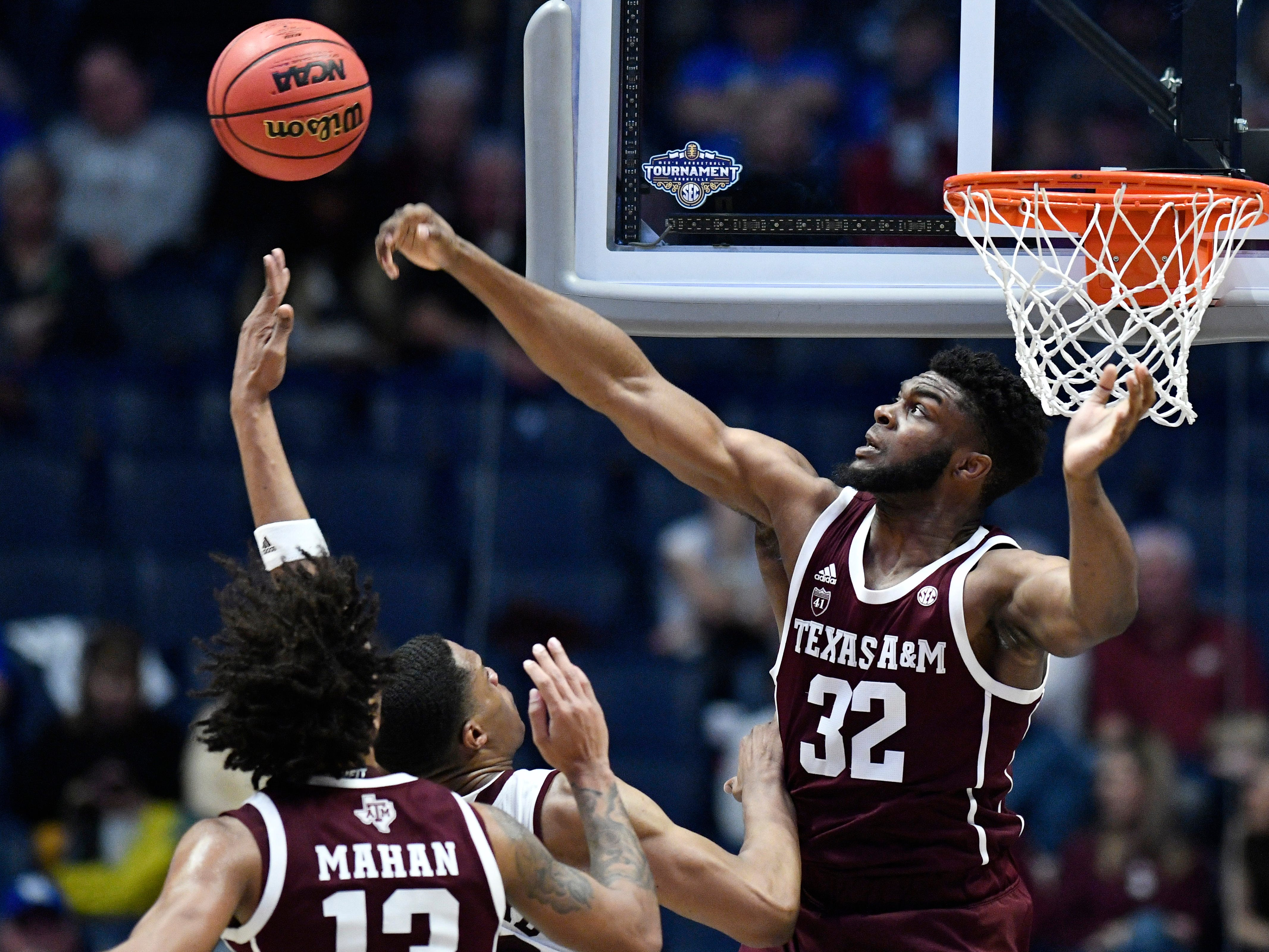 Texas A&M forward Josh Nebo (32) swats away a shot by Mississippi State guard Robert Woodard (12) during the first half of the SEC Men's Basketball Tournament game at Bridgestone Arena in Nashville, Tenn., Thursday, March 14, 2019.