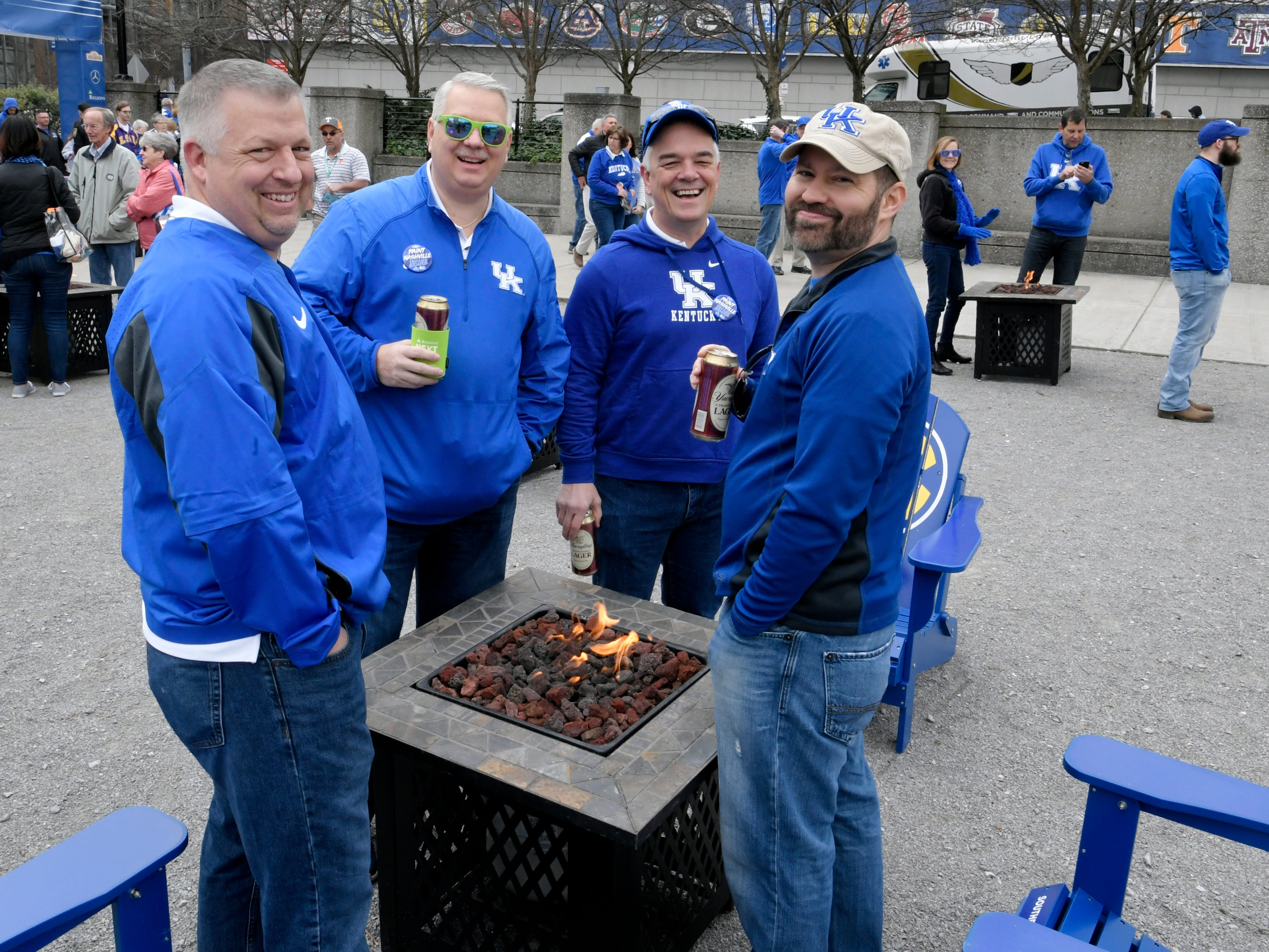 Kentucky fans gather around a fire at the SEC's Fanfare during the SEC Men's Basketball Tournament in Nashville on Friday, March 15, 2019.