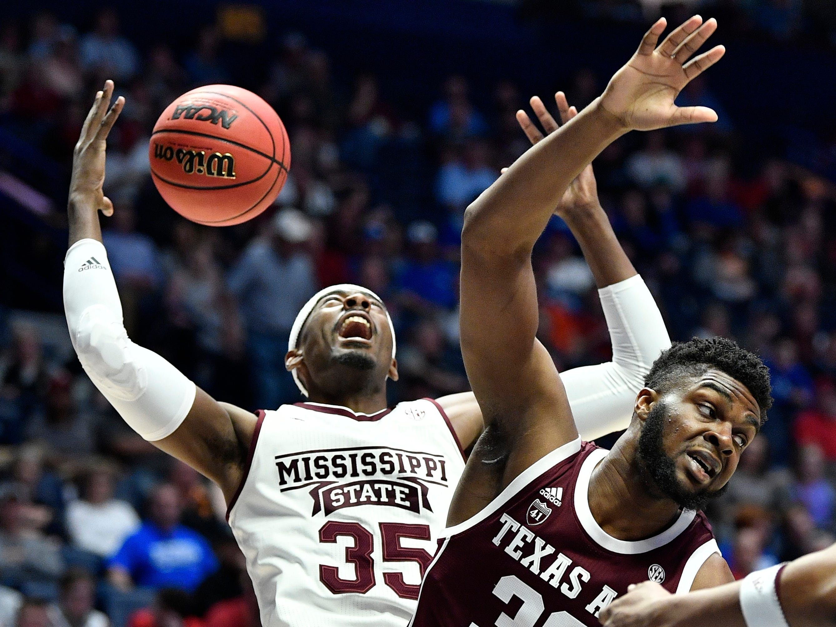 Mississippi State forward Aric Holman (35) and Texas A&M forward Josh Nebo (32) battle for the ball during the first half of the SEC Men's Basketball Tournament game at Bridgestone Arena in Nashville, Tenn., Thursday, March 14, 2019.
