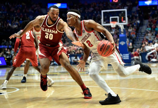 Ole Miss guard Devontae Shuler (2) moves the ball defended by Alabama forward Galin Smith (30) during the second half of the SEC Men's Basketball Tournament game at Bridgestone Arena in Nashville, Tenn., Thursday, March 14, 2019.